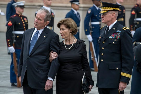 The family of former President George H.W. Bush, including former president George W. Bush (left) and former First Lady Laura Bush, watch as the casket is escorted following the funeral service on Thursday, Dec. 6, 2018, at St. Martin's Episcopal Church, Houston.