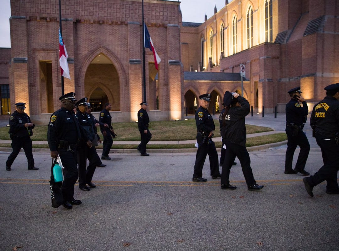 Police officers patrol the grounds of  St. Martin's Episcopal Church early Thursday, Dec. 6, 2018, as preparations are made for the funeral service of former President George H.W. Bush. in Houston, Texas.