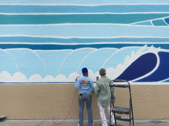 John Olvey and Kaleigh Glover painting their mural on the side of the Corpus Christi Trade Center on Dec. 6, 2018.