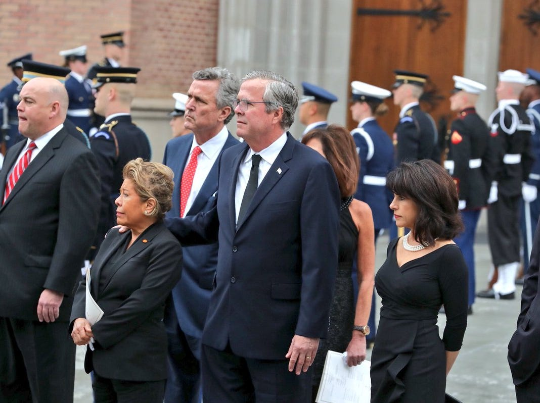 The family of former President George H.W. Bush including former Florida Gov. Jeb Bush (center) watch as the casket is led away outside St. Martin's Episcopal Church on Thursday, Dec. 6, 2018, in Houston, Texas.