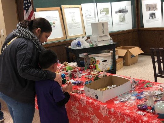 Two attendees inspect ornaments at the 21st Annual Tree of Angels in Nueces County.