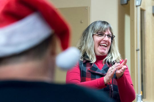 Linda Stepler claps during a multi-denominational holiday gathering at Acuity Specialty Hospital Wednesday, Dec. 5, 2018 in Willingboro, N.J. Stepler, who spent weeks there after nearly dying from Guillian-Barre syndrome at age 46 is now 51 and fully recovered. Stepler delivered holiday decorations made by her students at Haddonfield Friends School.