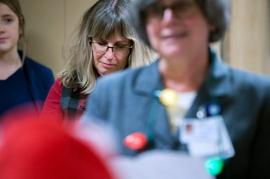 Linda Stepler lowers her head during a prayer at a multi-denominational holiday gathering at Acuity Specialty Hospital Wednesday, Dec. 5, 2018 in Willingboro, N.J. Stepler, who spent weeks there after nearly dying from Guillian-Barre syndrome at age 46 is now 51 and fully recovered. Stepler delivered holiday decorations made by her students at Haddonfield Friends School.