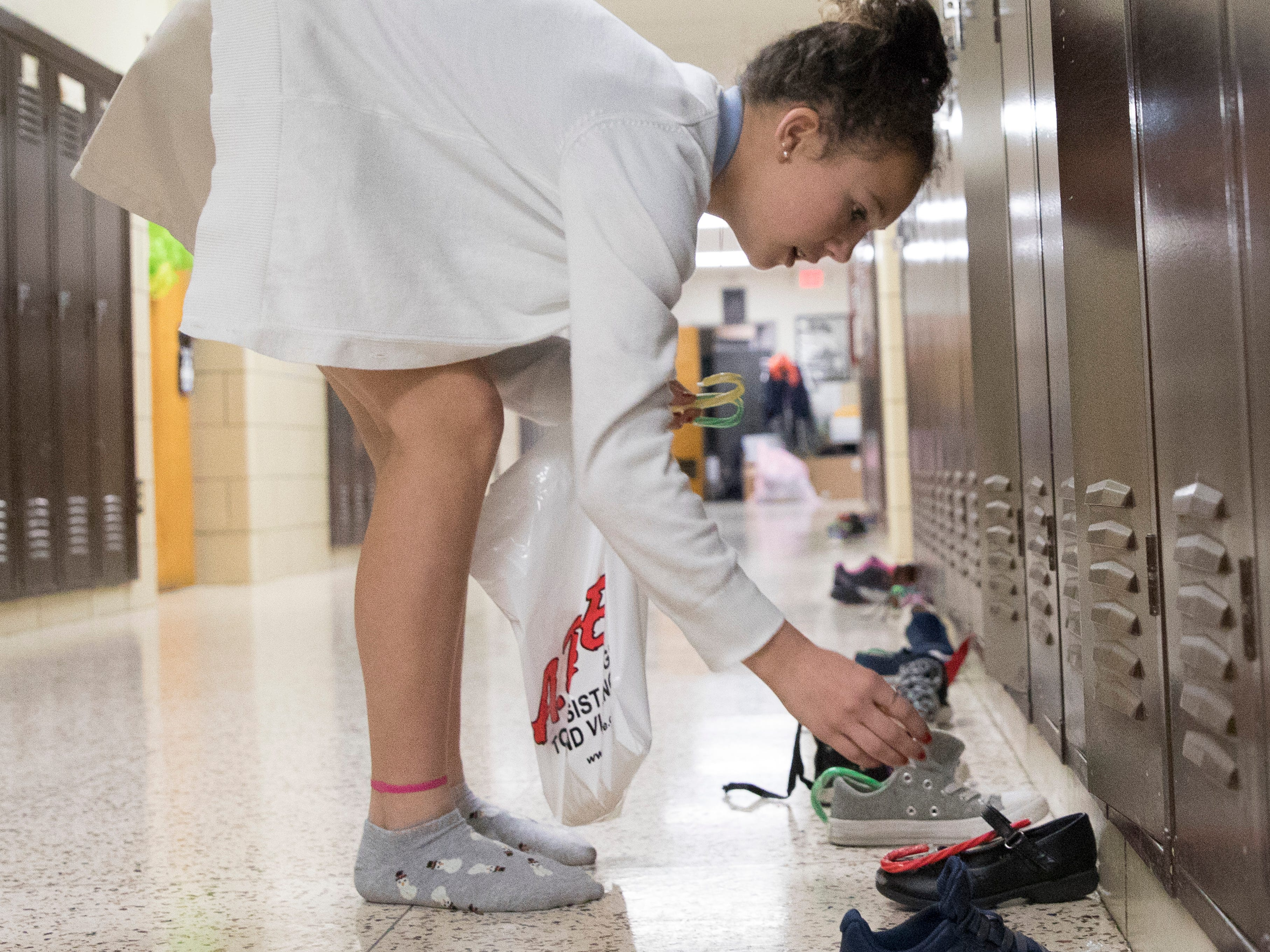 Ella Mikus helps St. Nicholas put candy canes inside the children's shoes at Bishop Flaget Middle School the morning of December 6, 2018. Today, St. Nicholas is recognized as the originator of Santa Claus and was known for his generosity and love of children by using his inheritance to help the needy, sick, and suffering.