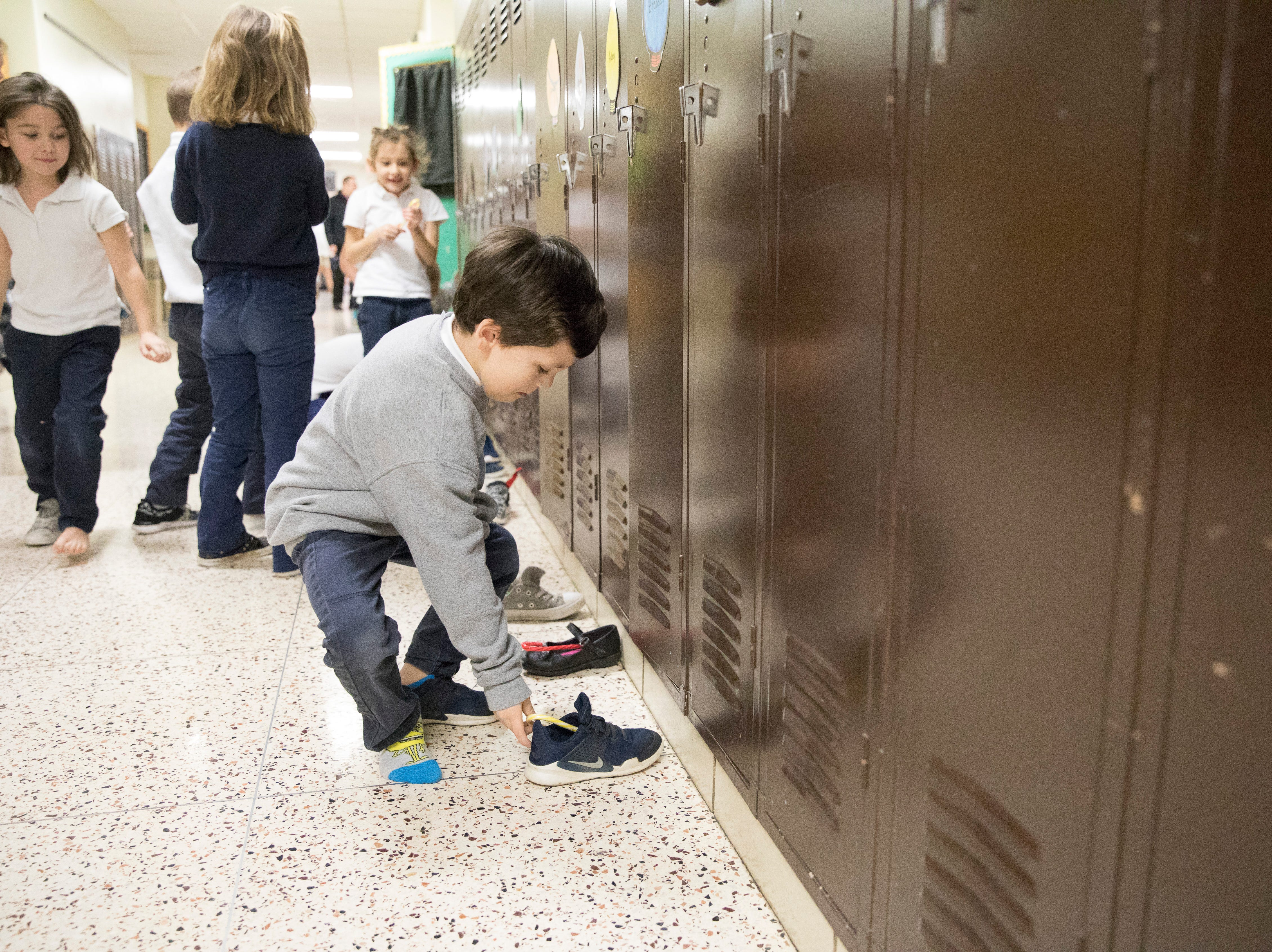 Bransen Kight picks up his shoes outside the hallway after candy canes were left by St. Nicholas at Bishop Flaget Middle School on December 6, 2018. Today, St. Nicholas is recognized as the originator of Santa Claus and was known for his generosity and love of children by using his inheritance to help the needy, sick, and suffering.