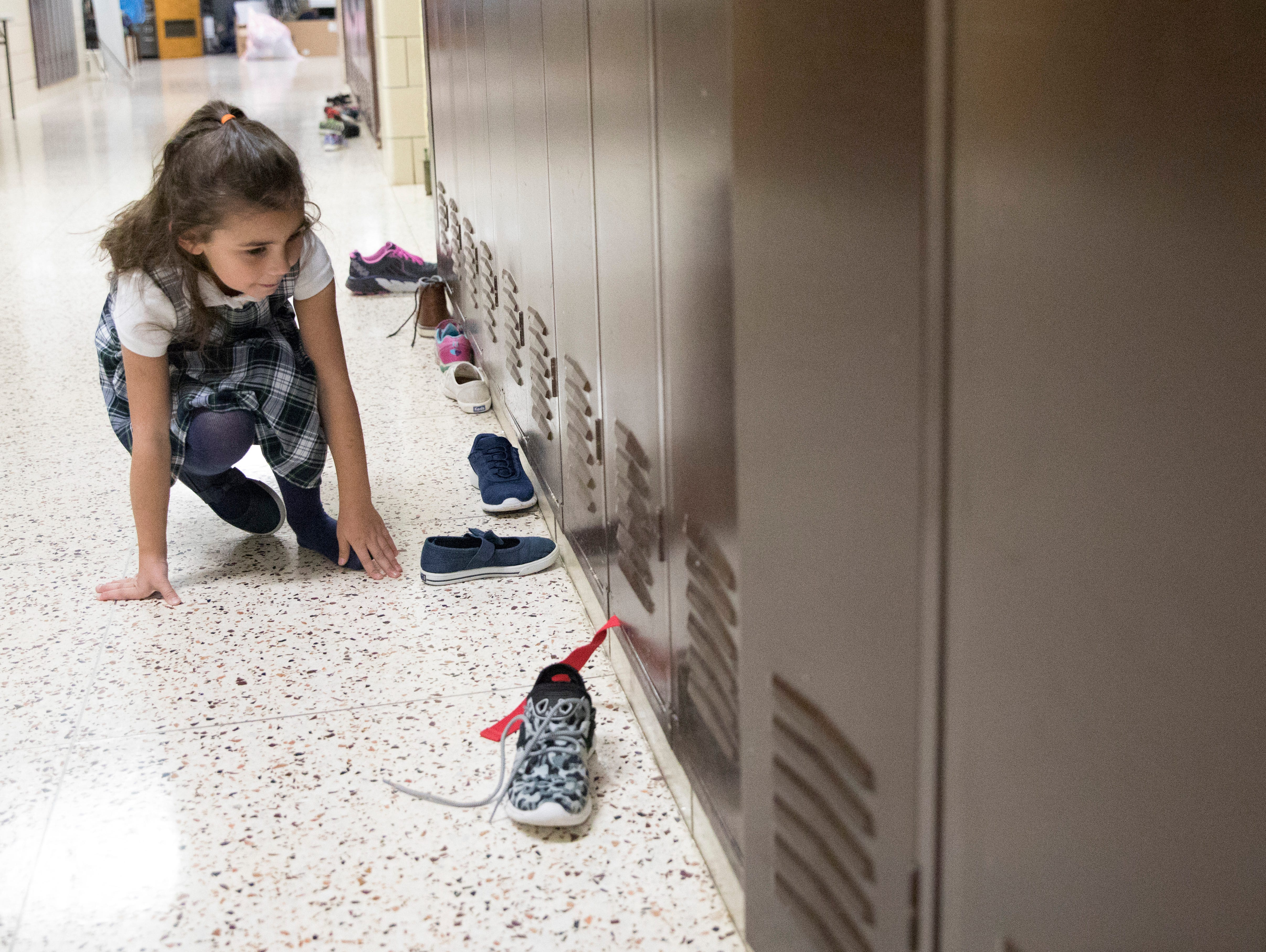 Anaya Tedesco carefully places her shoes in the hallway outside of class as she and other students wait for a special gift from St. Nicholas at Bishop Flaget Middle School the morning of December 6, 2018. Today, St. Nicholas is recognized as the originator of Santa Claus and was known for his generosity and love of children by using his inheritance to help the needy, sick, and suffering.