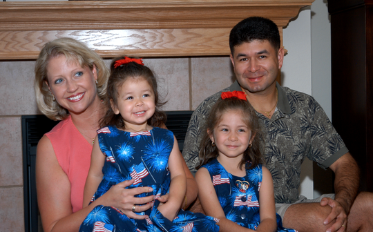 Cristie Escandon (left) and her two daughters, Grace, and Alyssa, and husband, Ric, in 2003. The girls wear matching American flag dresses with their father, a pilot, just before a deployment in the U.S. Navy.