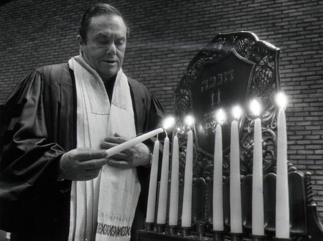 Rabbi Albert A. Goldman of Isaac M. Wise Temple lights the eight candles of the menorah in 1979.