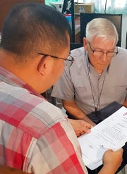 In this Dec. 5, 2018, photo released by the Bureau of Immigration Public Information Office, Roman Catholic priest Rev. Kenneth Bernard Hendricks, right, looks at documents after being arrested in a church in Naval town in the island province of Biliran, central Philippines.