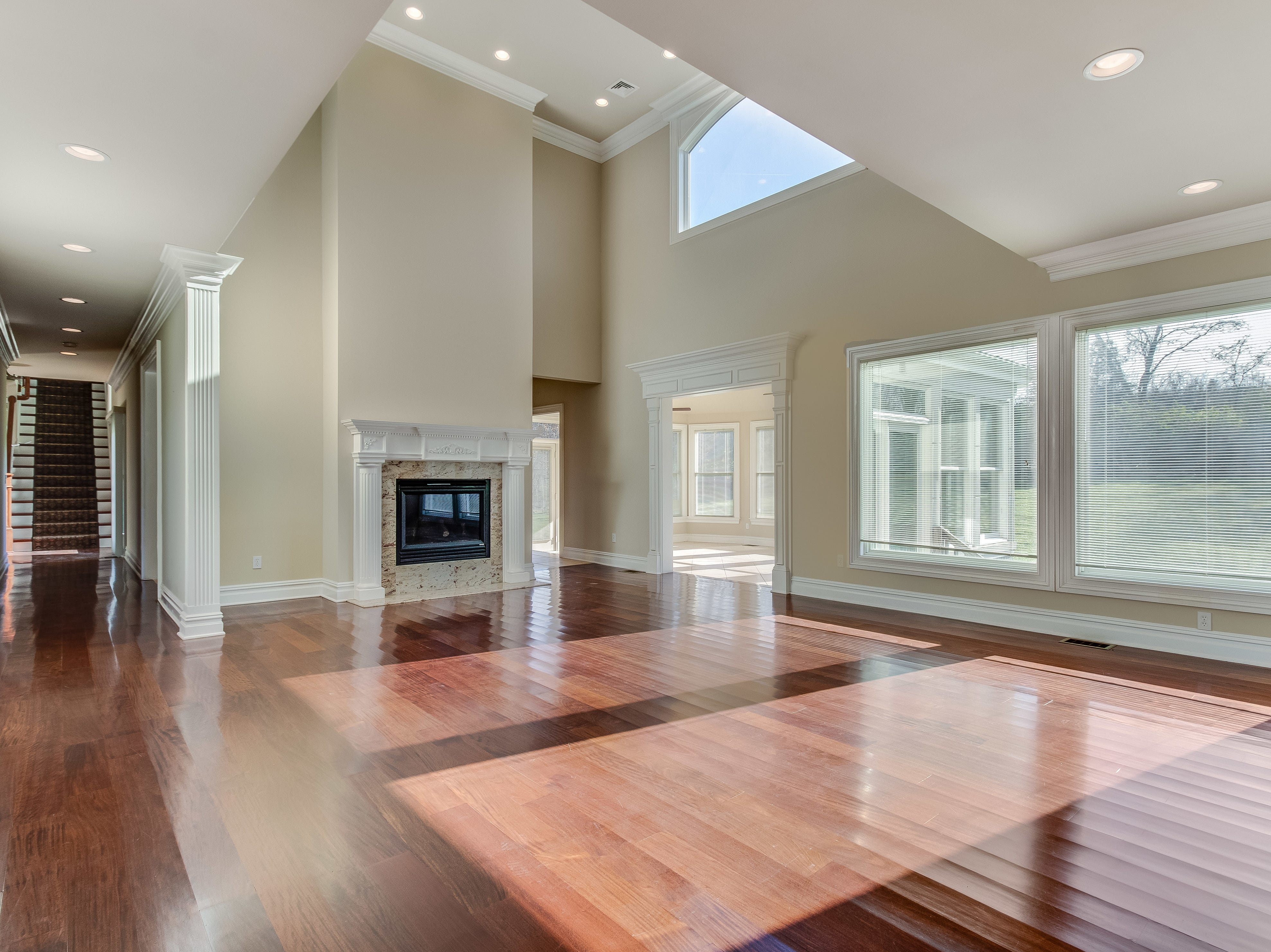 The family room of this 15-room estate home has a volume ceiling, a two-story fireplace, walls of windows overlooking the private backyard and hardwood floors.