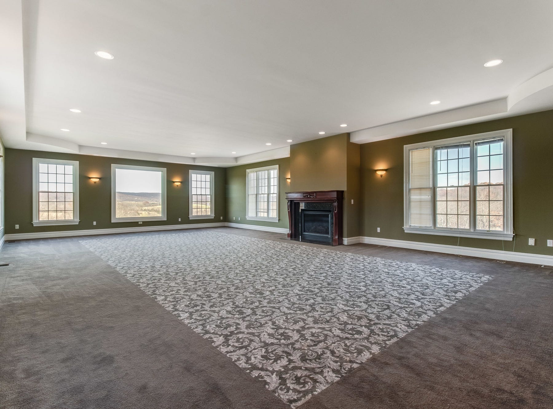 The Media Room has recessed lights in a tray ceiling, wall sconces, divided-light and picture windows on three sides and a fireplace.