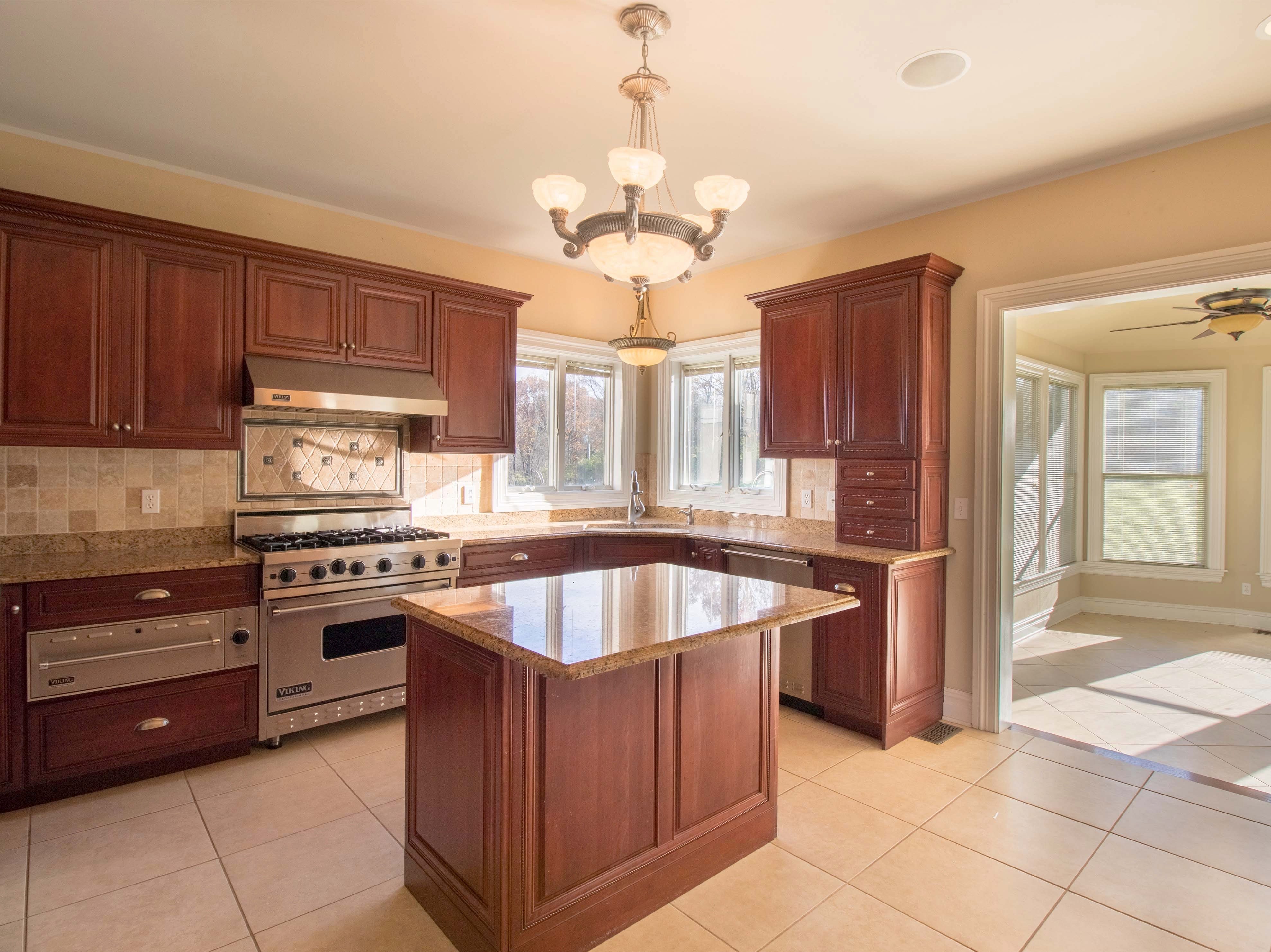The kitchen has raised-panel cabinets with granite counters, a center island with a breakfast bar, pendant and recessed lights, stainless-steel appliances and ceramic-tile floors.