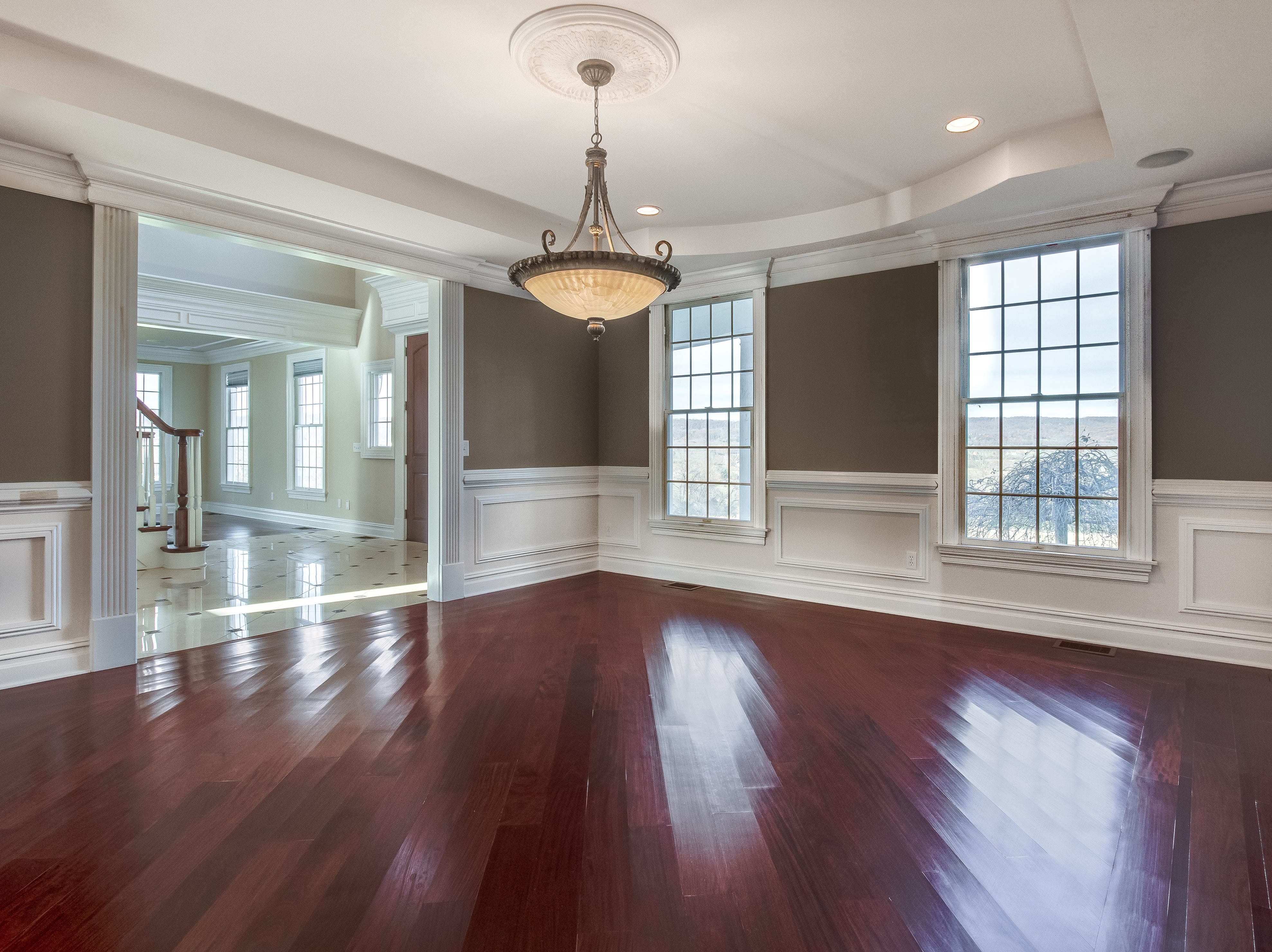 The  banquet-size formal dining room off the foyer has wainscoting, a tray ceiling with pendant and recessed lighting, large divided light windows and gleaming hardwood floors.