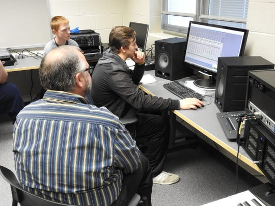 John Lindig leads student Duke Young through a mixing project as Dylan Bryant looks on. A sound engineering class, unique on the high school level, is in its second year at Ridgewood. Students learn how to record and mix songs.