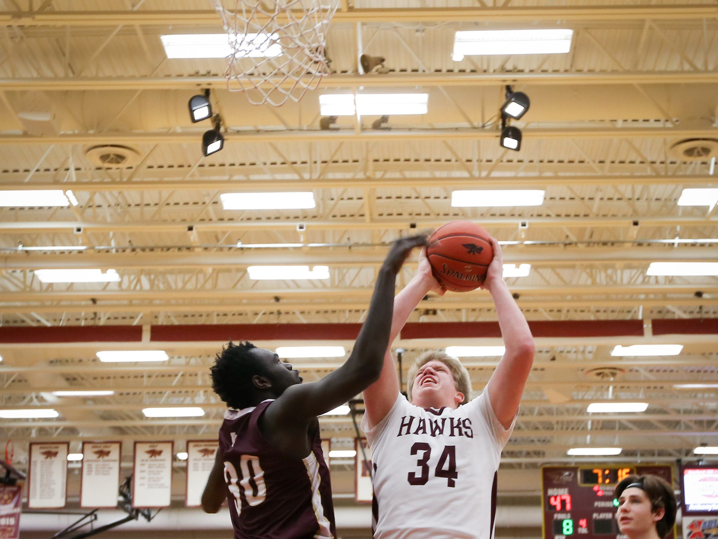 Ankeny junior Nolan Otten goes for a field goal past Lincoln junior Maiwut Jock during a boys high school basketball game between the Lincoln Railsplitters and the Ankeny Hawks at Ankeny High School on Dec. 4, 2018 in Ankeny, Iowa.