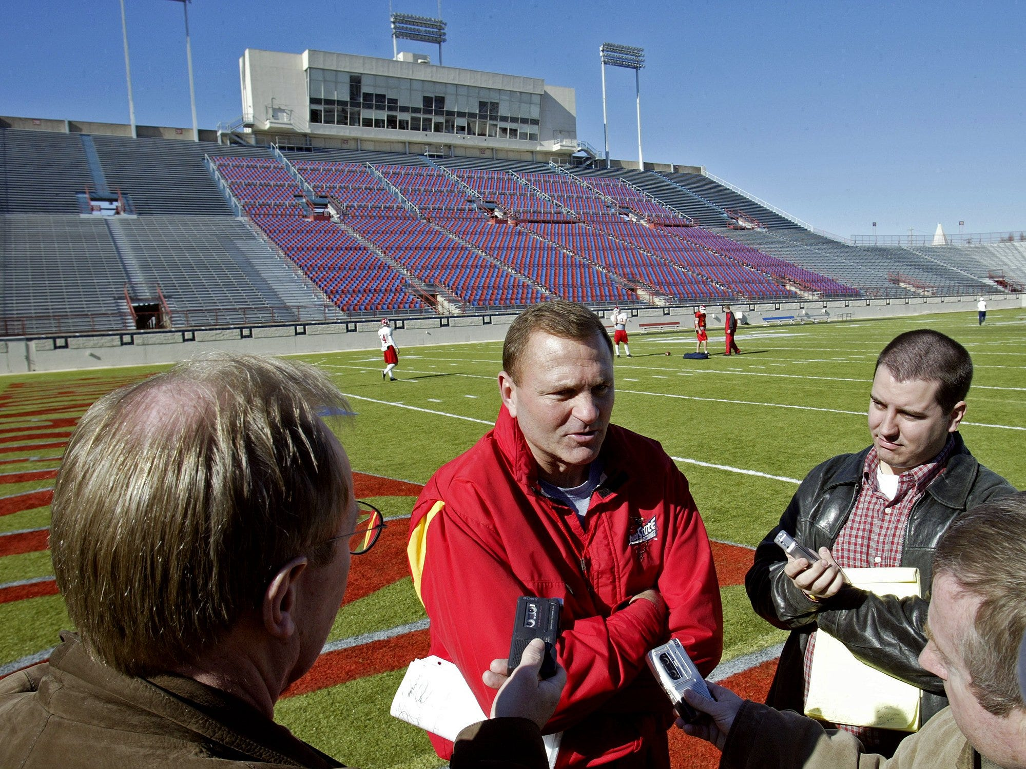 Iowa State head football coach Dan McCarney, center, answers questions from media members after his team finished practice in preparation for the 2004 Independence Bowl.