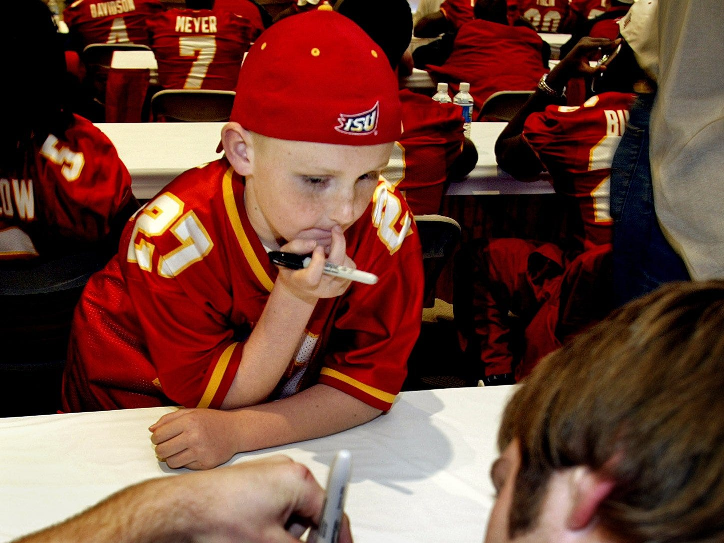 You're from where? Chad Cotton Whitehead of Austin, Texas, 9-year-old nephew of Iowa State coach Barney Cotton, has his football autographed by Iowa State's Nick Frere before the 2004 Independence Bowl.