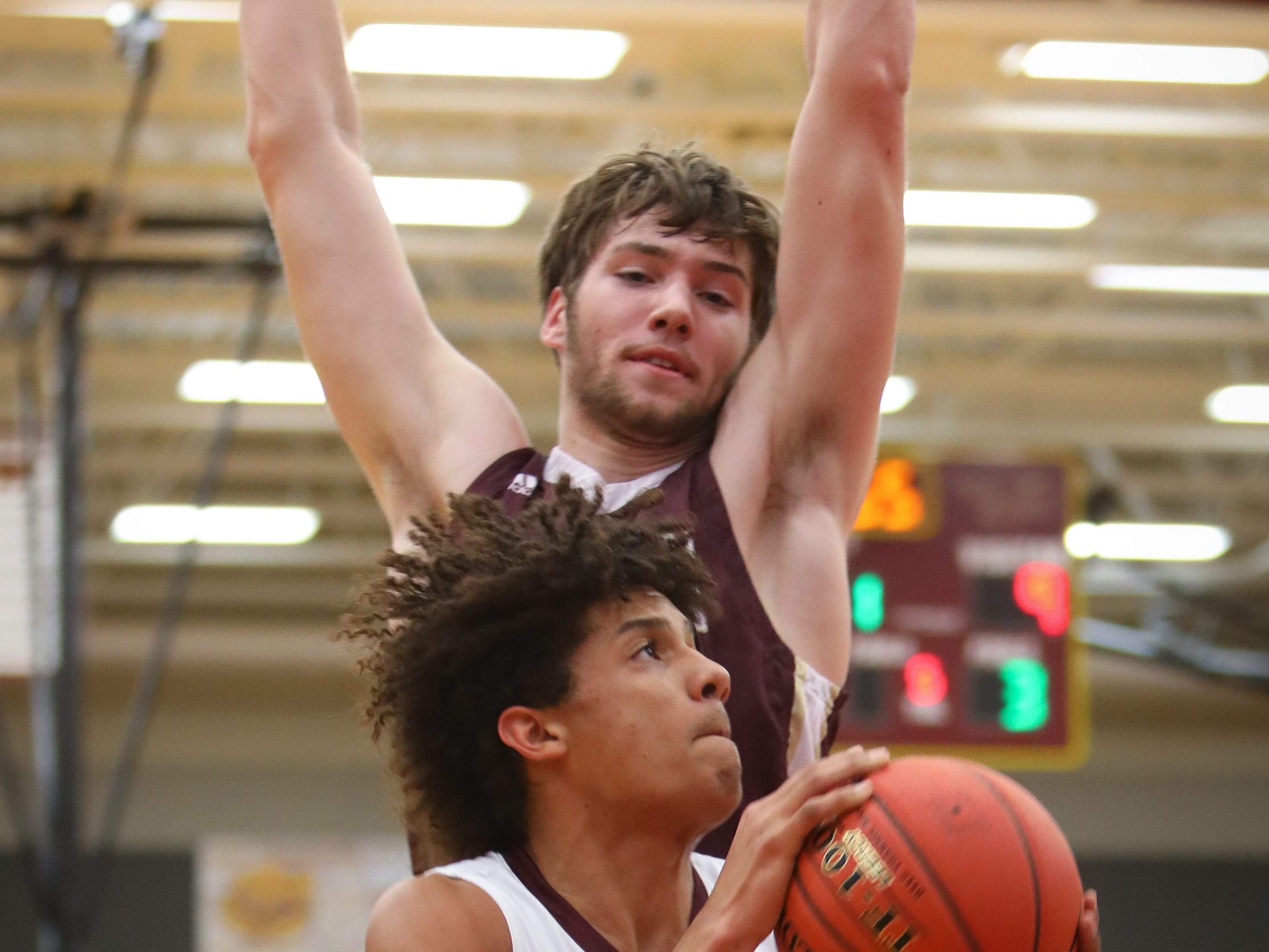 Ankeny junior Braxton Bayless goes for a lay-up past Lincoln senior Logan Sharp during a boys high school basketball game between the Lincoln Railsplitters and the Ankeny Hawks at Ankeny High School on Dec. 4, 2018 in Ankeny, Iowa.