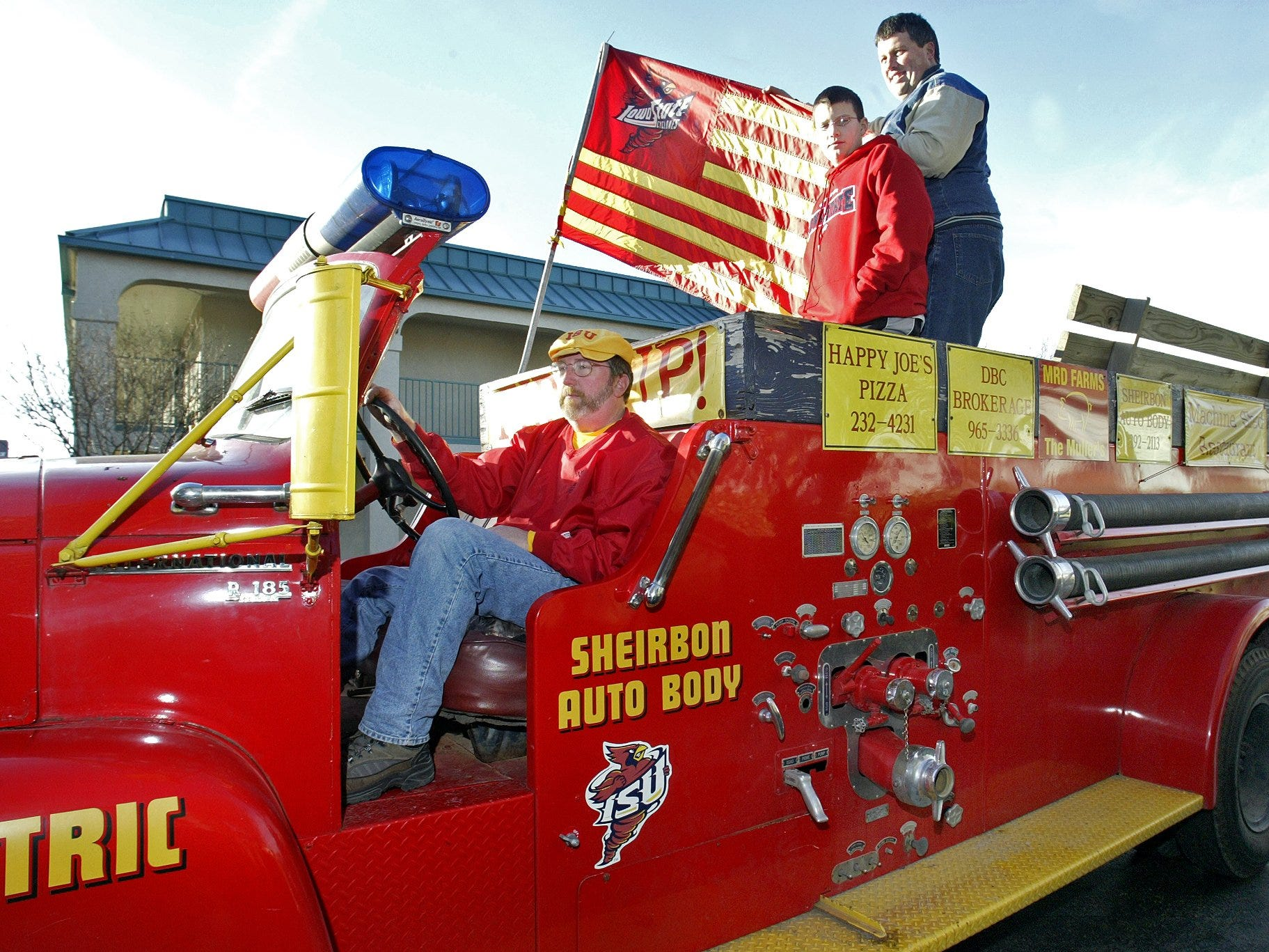 Iowa State fans Tim Gleason, left, and Chuck Noty and son Christopher ride Gleason's 1957 firetruck before a pep rally in Shreveport for the 2004 Independence Bowl.