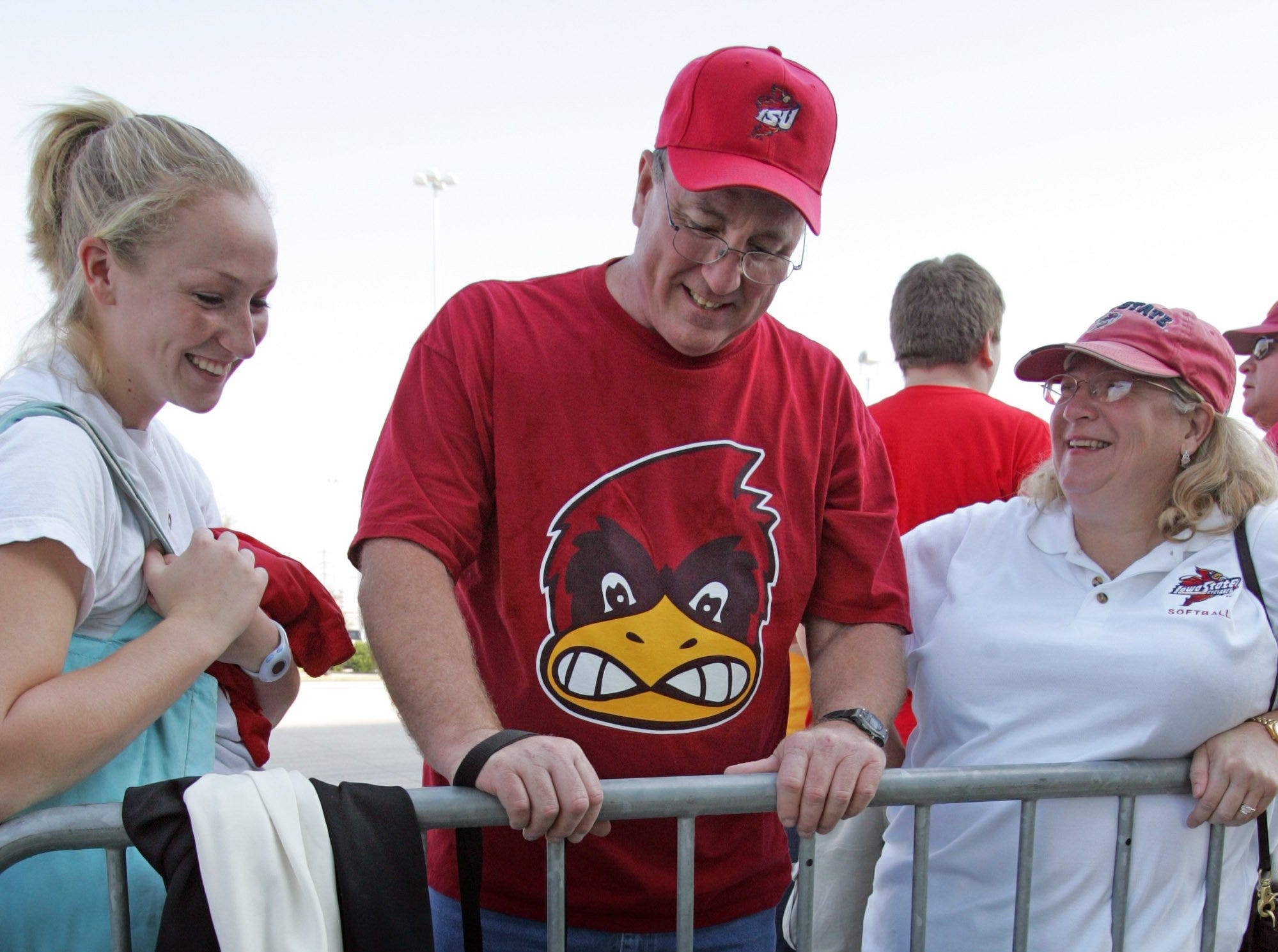 From 2005: The Ransom family of Round Rock, Texas, looks at a game program. Alyssa Ransom, left, plays softball for Iowa State. Randy and Carole Ransom are her parents.
