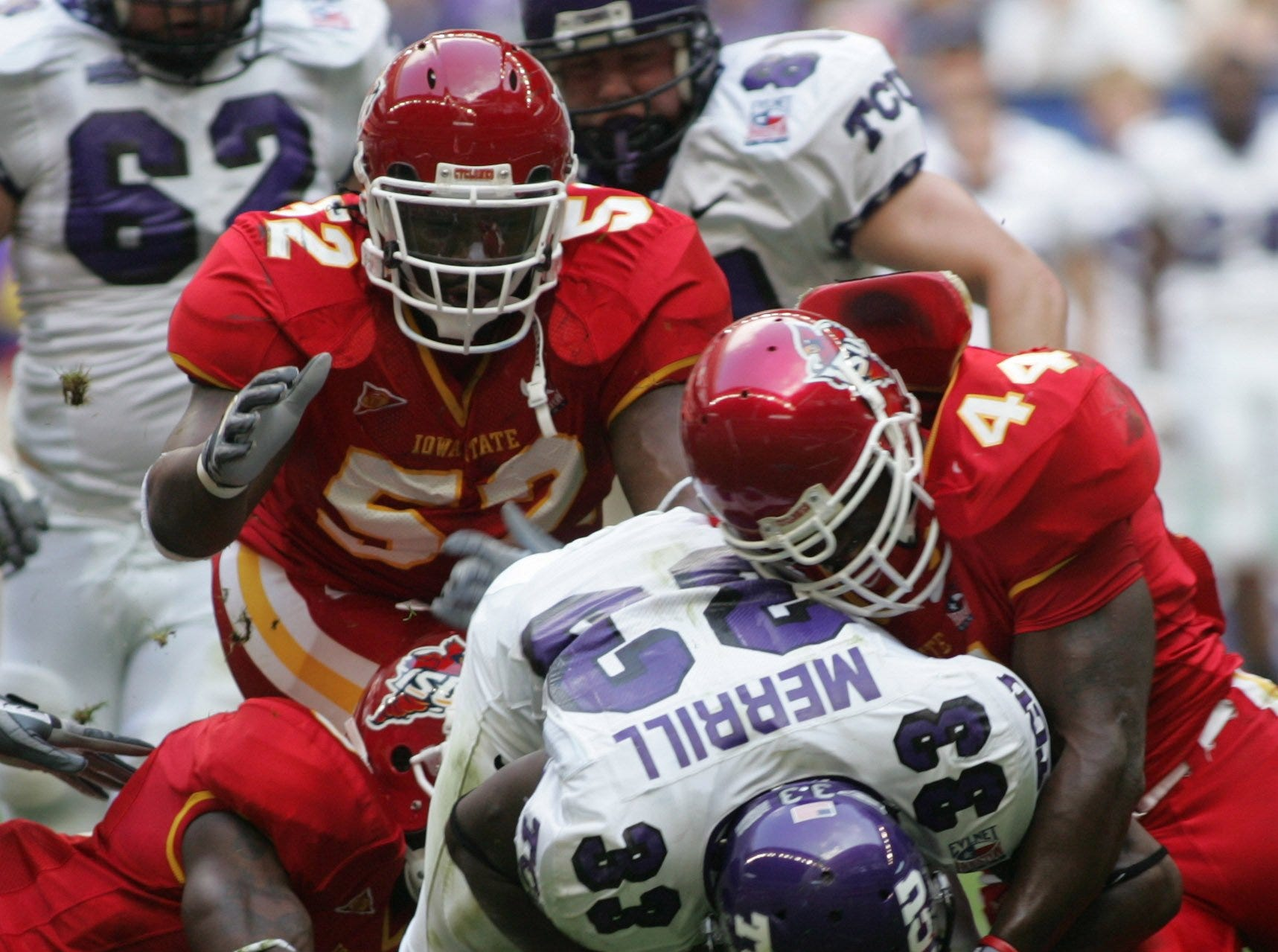 TCU running back Robert Merrill is brought down by Iowa State's Brent Curvey (52), Tim Dobbins (44) and others during the 2005 Houston Bowl.