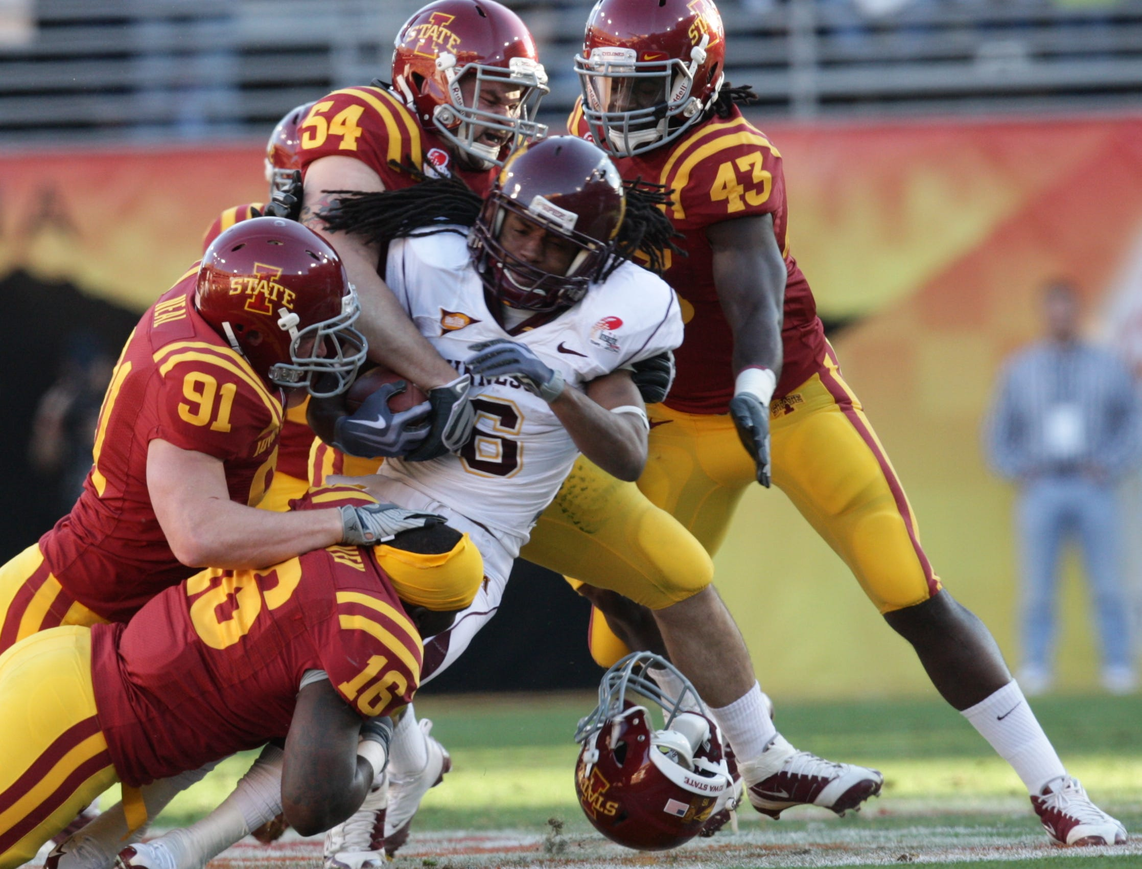 ISU's (16)Josh Raven (91)Patrick Neal (54)Jesse Smith and (43)Fred Garrin wrap up Minnesota's (6) Kevin Whaley. (16) Josh Raven lost his helmet on the play. S0101ISUBowl -Iowa State University played Minnesota in the Insight Bowl in Tempe, Arizona, Thursday, December 31, 2009 at Sun Devil Stadium. (Andrea Melendez/The Register)