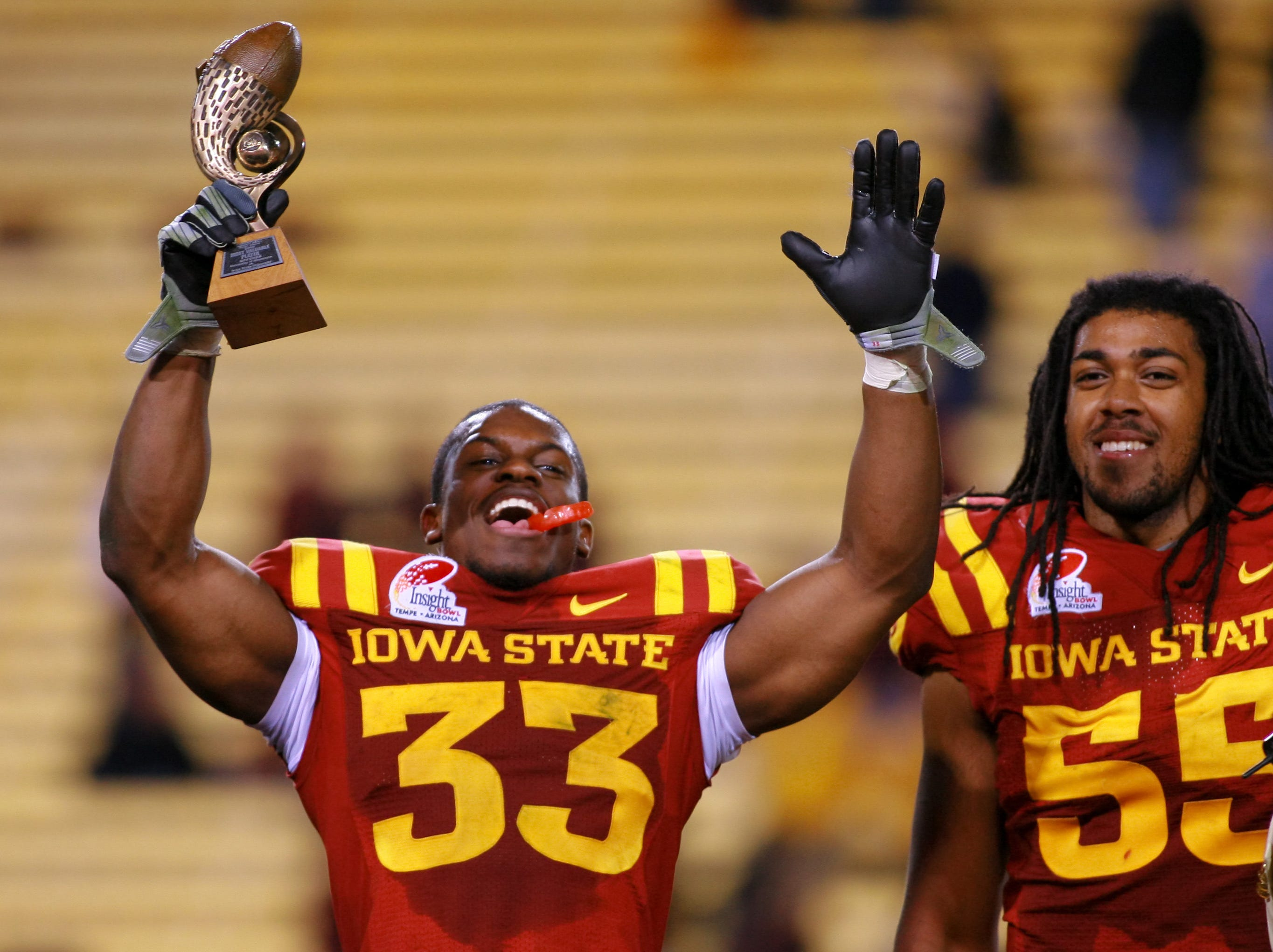 Dec 31, 2009; Tempe, AZ, USA; Iowa State Cyclones running back Alexander Robinson (33) holds up the trophy for most outstanding offensive player in the 2009 Insight Bowl.  The Cyclones defeated the Minnesota Golden Gophers 14-13 at Sun Devil Stadium.  Mandatory Credit: Chris Morrison-USA TODAY Sports