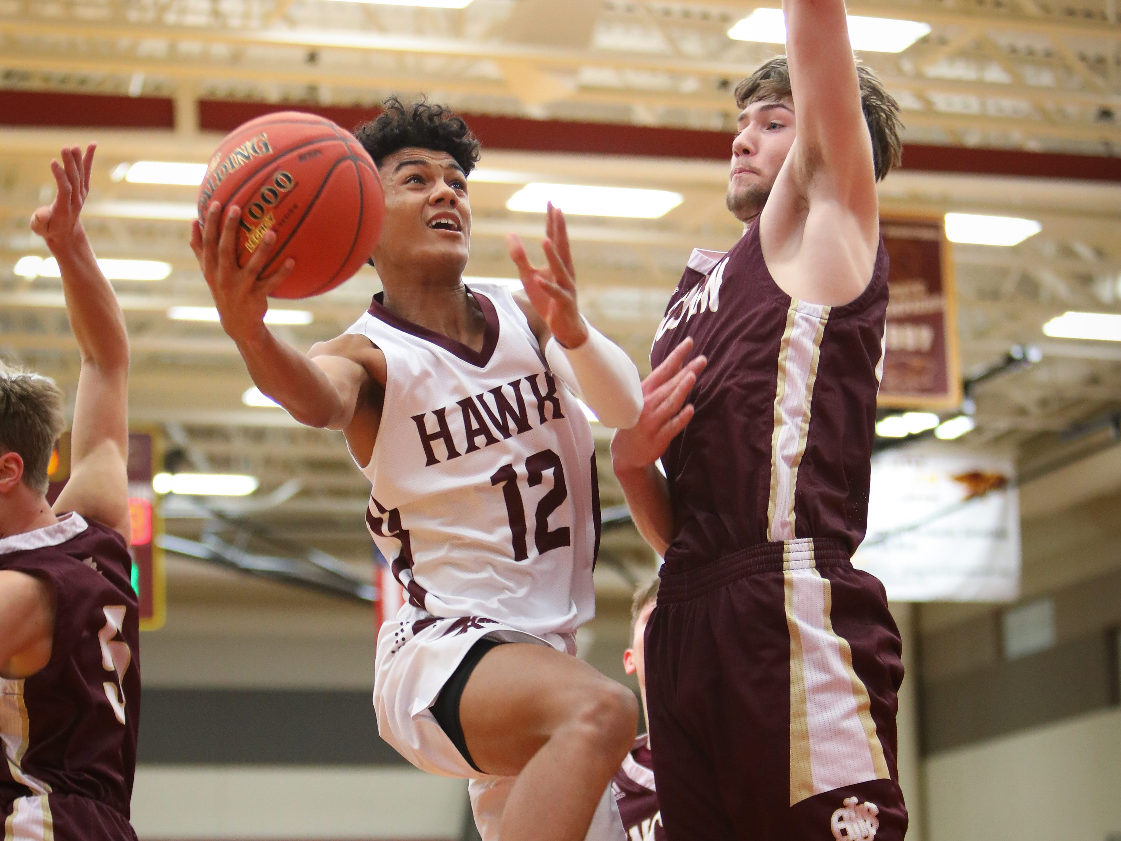 Ankeny junior Jaxon Smith goes for a lay-up past Lincoln senior Logan Sharp during a boys high school basketball game between the Lincoln Railsplitters and the Ankeny Hawks at Ankeny High School on Dec. 4, 2018 in Ankeny, Iowa.