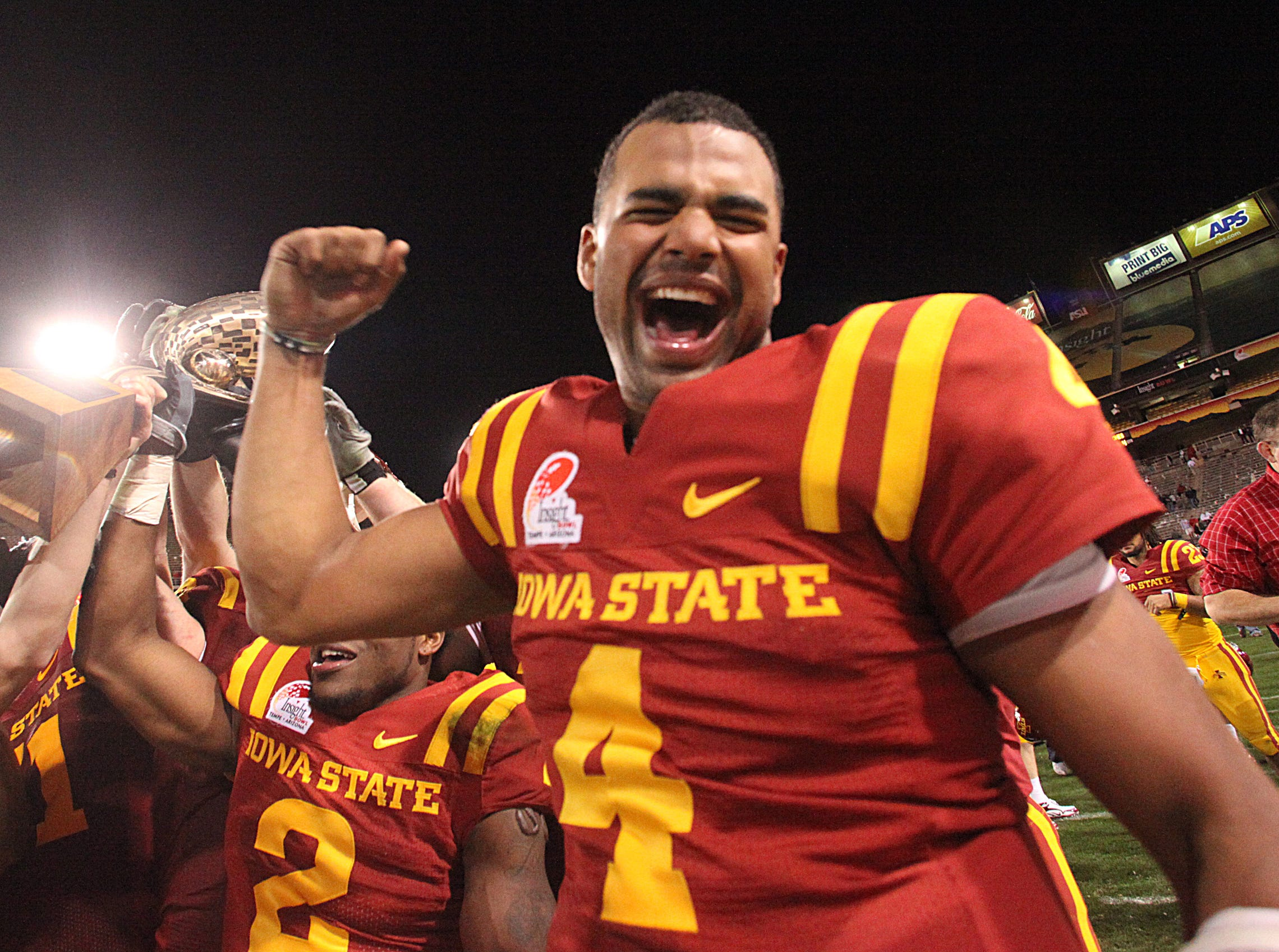Austen Arnaud and the rest of the ISU team celebrate their win with the trophey. Iowa State won 14-13. S0101ISUBowl -Iowa State University played Minnesota in the Insight Bowl in Tempe, Arizona, Thursday, December 31, 2009 at Sun Devil Stadium. (Andrea Melendez/The Register)