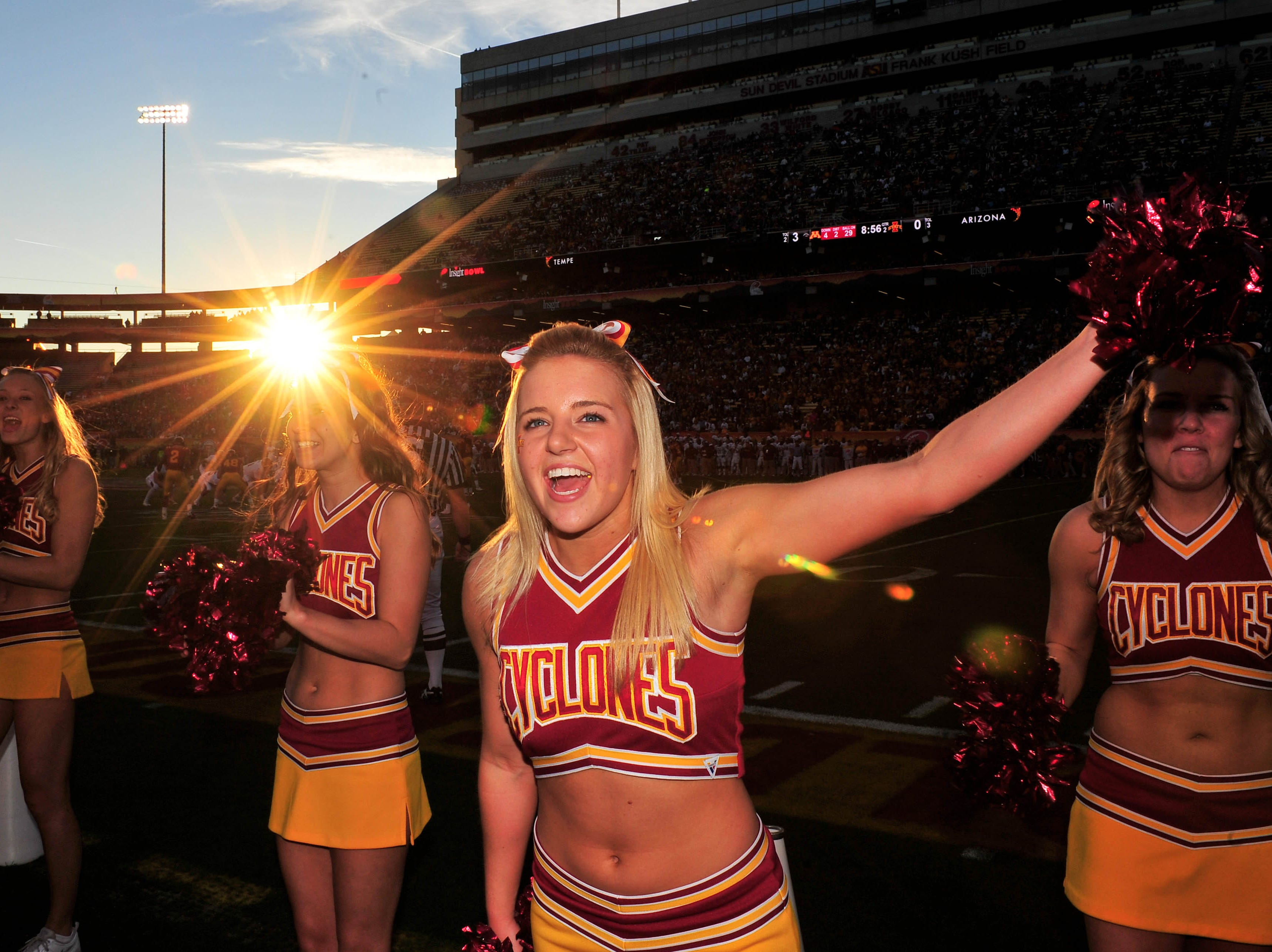 Dec 31, 2009; Tempe, AZ, USA; An Iowa State Cyclones cheerleader cheers on her team as the sun sets behind Sun Devil Stadium during the 2nd quarter of a game against the Minnesota Golden Gophers in the 2009 Insight Bowl.  Mandatory Credit: Chris Morrison-USA TODAY Sports