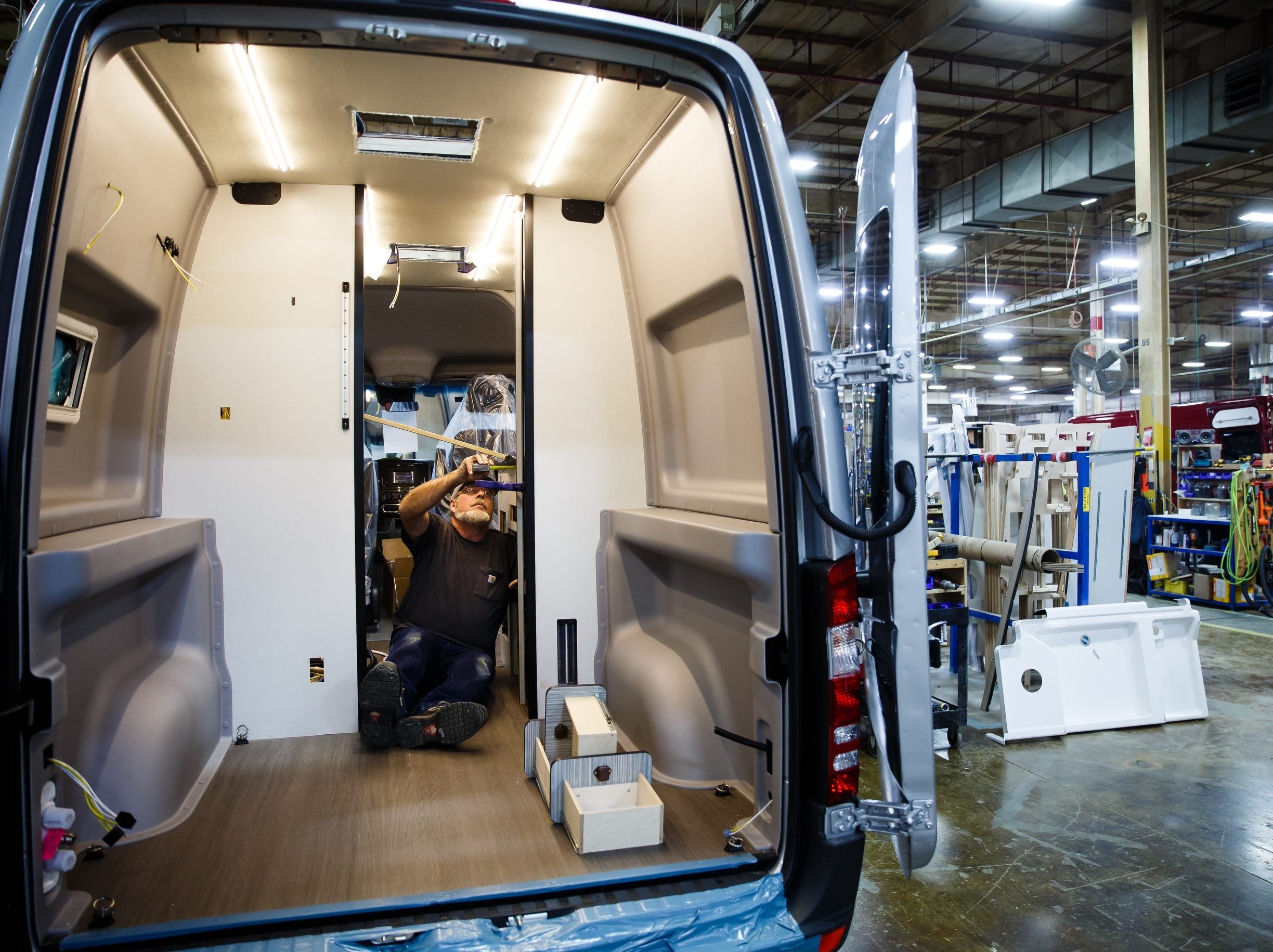 Workers install the kitchen cabinet on the Winnebago Revel at the companies Lake Mills factory on Wednesday, Dec. 5, 2018. The Revel, with its 4x4 and rugged nature has sparked the interest of outdoor enthusiasts and has helped the motor home manufacture rebound from poor sales during the recession.