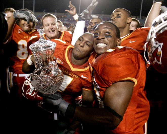 Iowa State's Ellis Hobbs, right, shoots a big grin to the cameras as he and teammate Tyson Smith hold the crystal trophy Tuesday after defeating Miami of Ohio in the 2004 Independence Bowl.