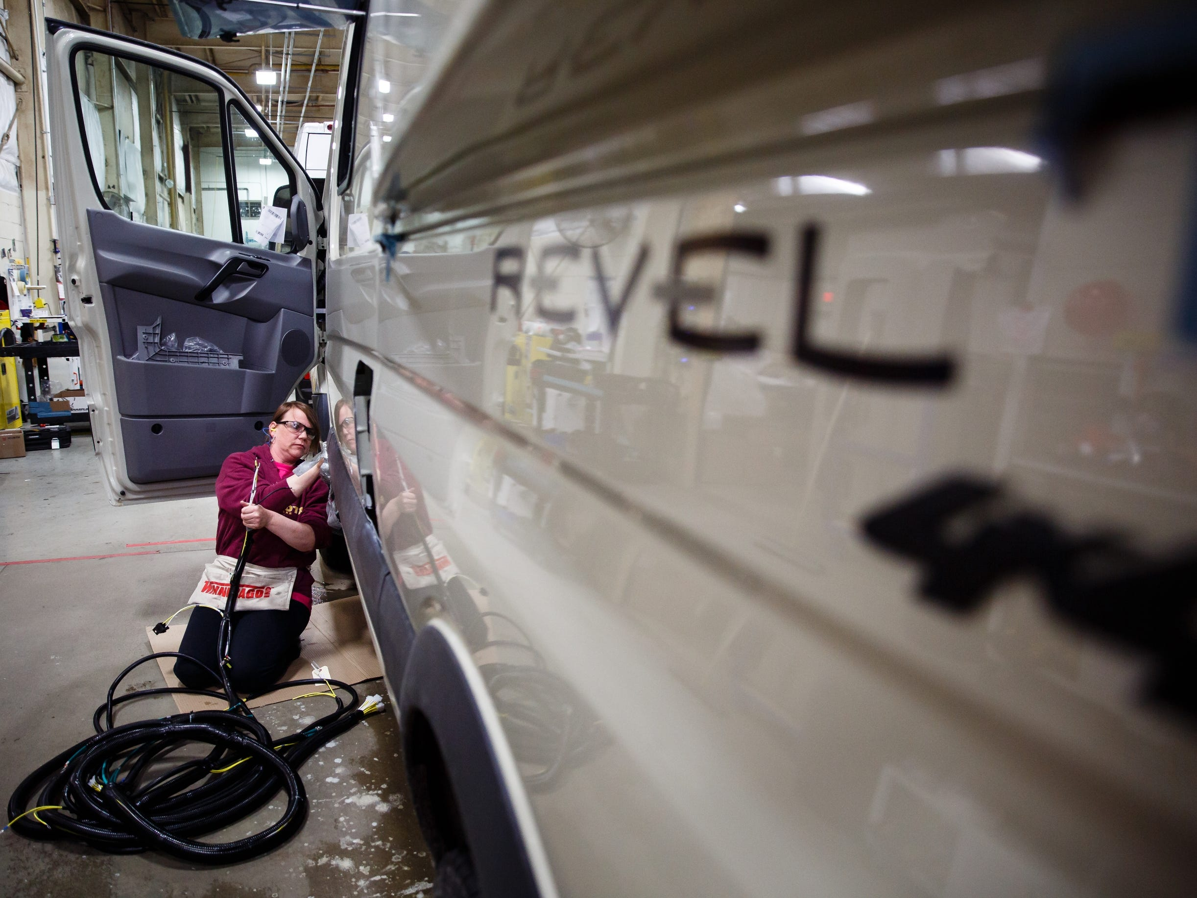 Workers install a wiring harness on the Winnebago Revel at the companies Lake Mills factory on Wednesday, Dec. 5, 2018. The Revel, with its 4x4 and rugged nature has sparked the interest of outdoor enthusiasts and has helped the motor home manufacture rebound from poor sales during the recession.