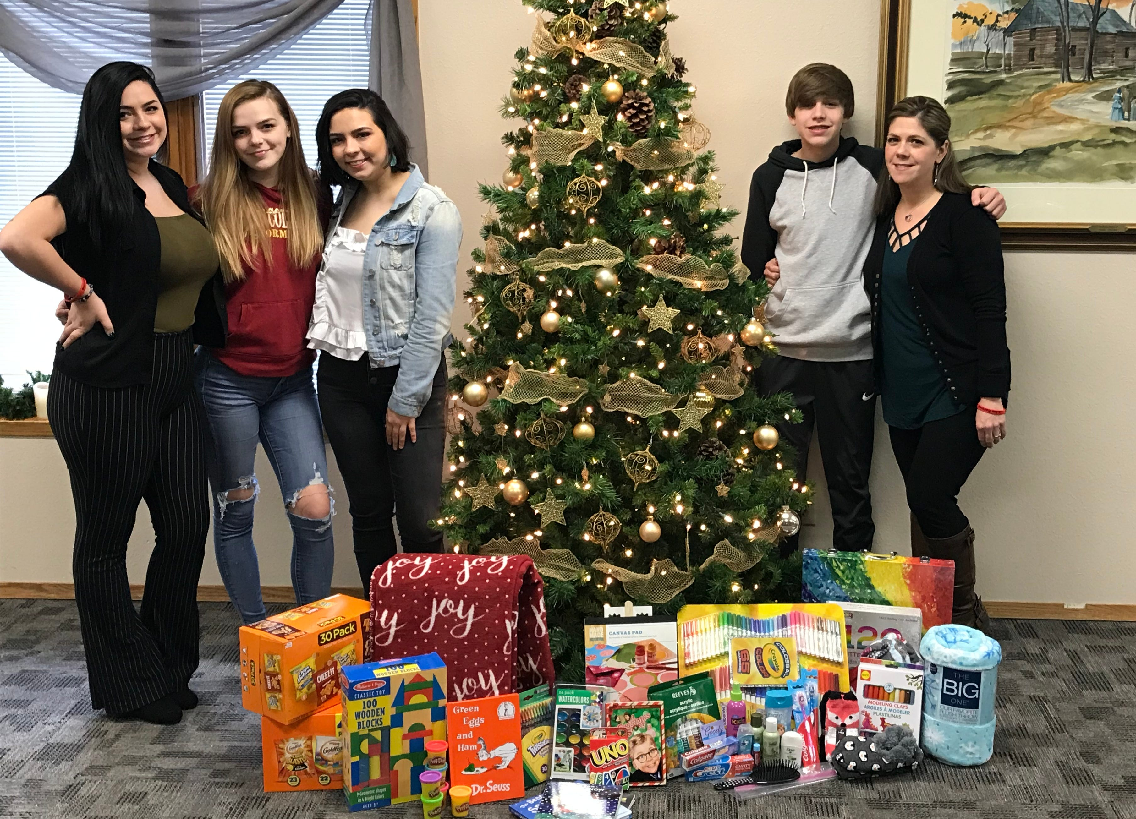 "From left, Molly, Juliana, Maddie and Josh Livingston and their mother, Amber Hayes, stand near some of the items donated for their ""Spreading Joy for Joe"" drive. The family will hand out gift bags to families at Blank Children's Hospital on Christmas Eve in memory of Joseph Livingston, who died last year in a car crash."