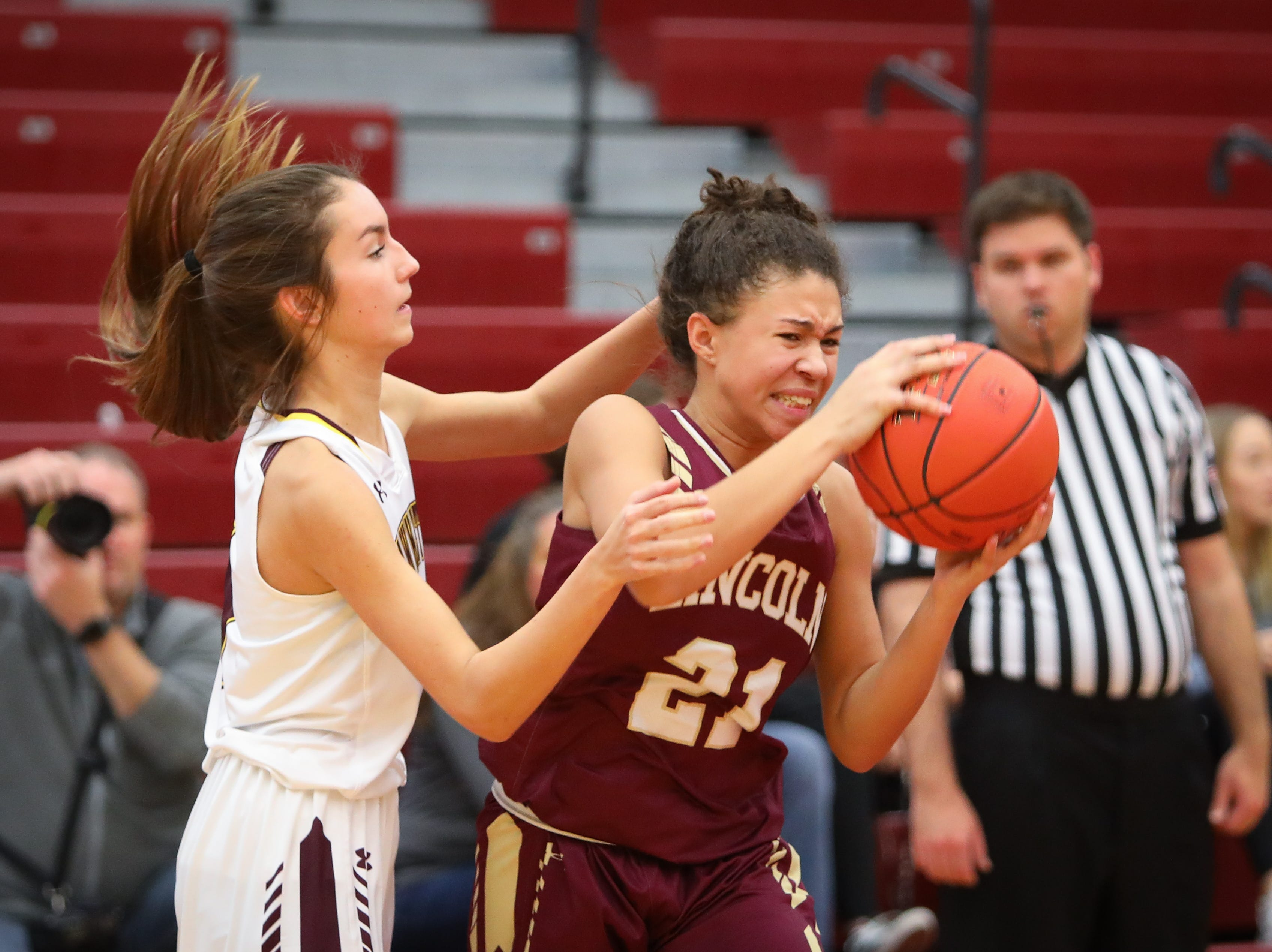 Lincoln sophomore Jalyiah Miller keeps the ball away from Ankeny junior Kayla Pitz during a girls high school basketball game between the Lincoln Railsplitters and the Ankeny Hawks at Ankeny High School on Dec. 4, 2018 in Ankeny, Iowa.