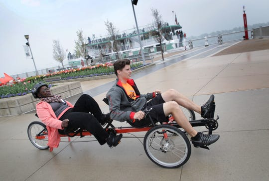 Georgea Cole, left and Jared Long ride a recumbent tandem on the Detroit riverfront on Tuesday, May 15, 2018. MoGo launched its bike share program in 2017 and has added an Adaptive MoGo bike share program, too.