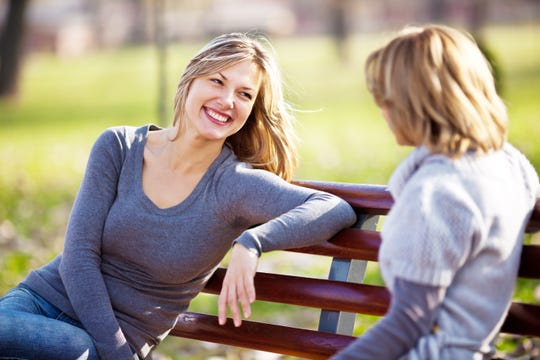 Two cheerful  women sitting on the bench in the park and having a conversation.