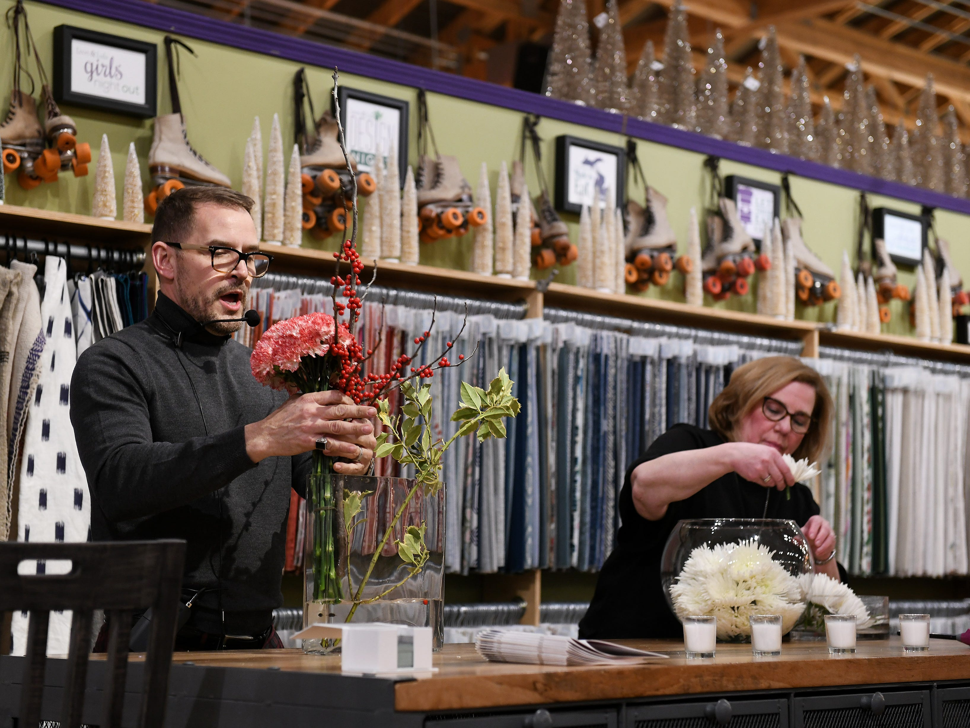 Denise Boreczky helps fill a glass bowl with flowers while Jeffrey Jucewicz of Jeffrey Floral Architecture shows how simple and elegant a centerpiece can be made, this one with carnations and holly.