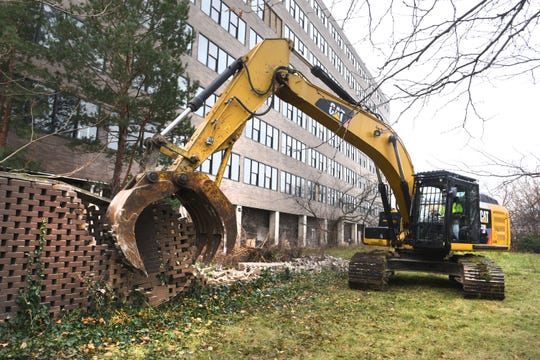 Heavy equipment takes down a wall.