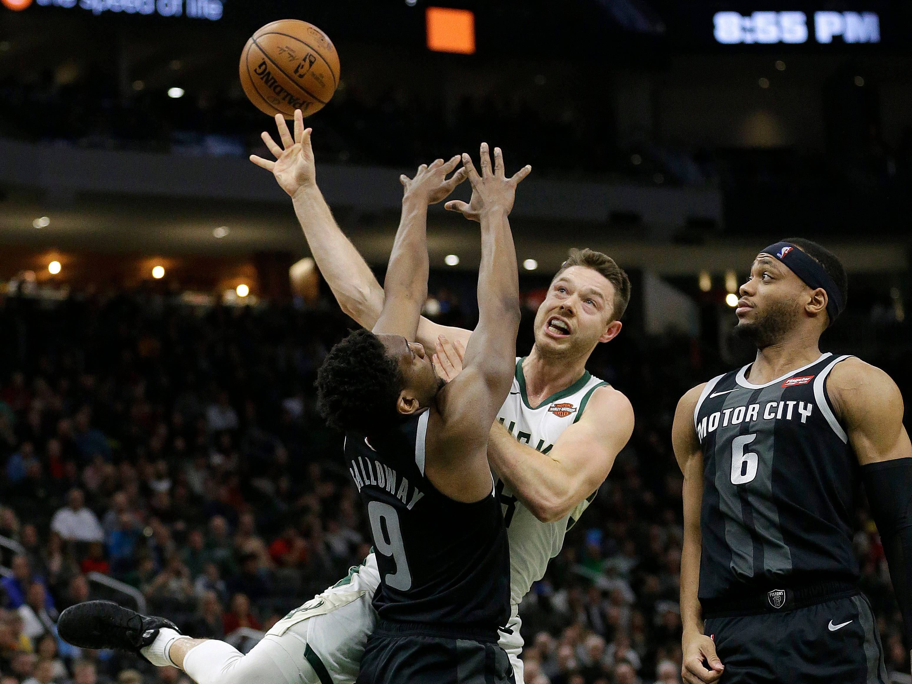 Milwaukee's Matthew Dellavedova, middle, is fouled between Detroit's Langston Galloway (9) and Bruce Brown.