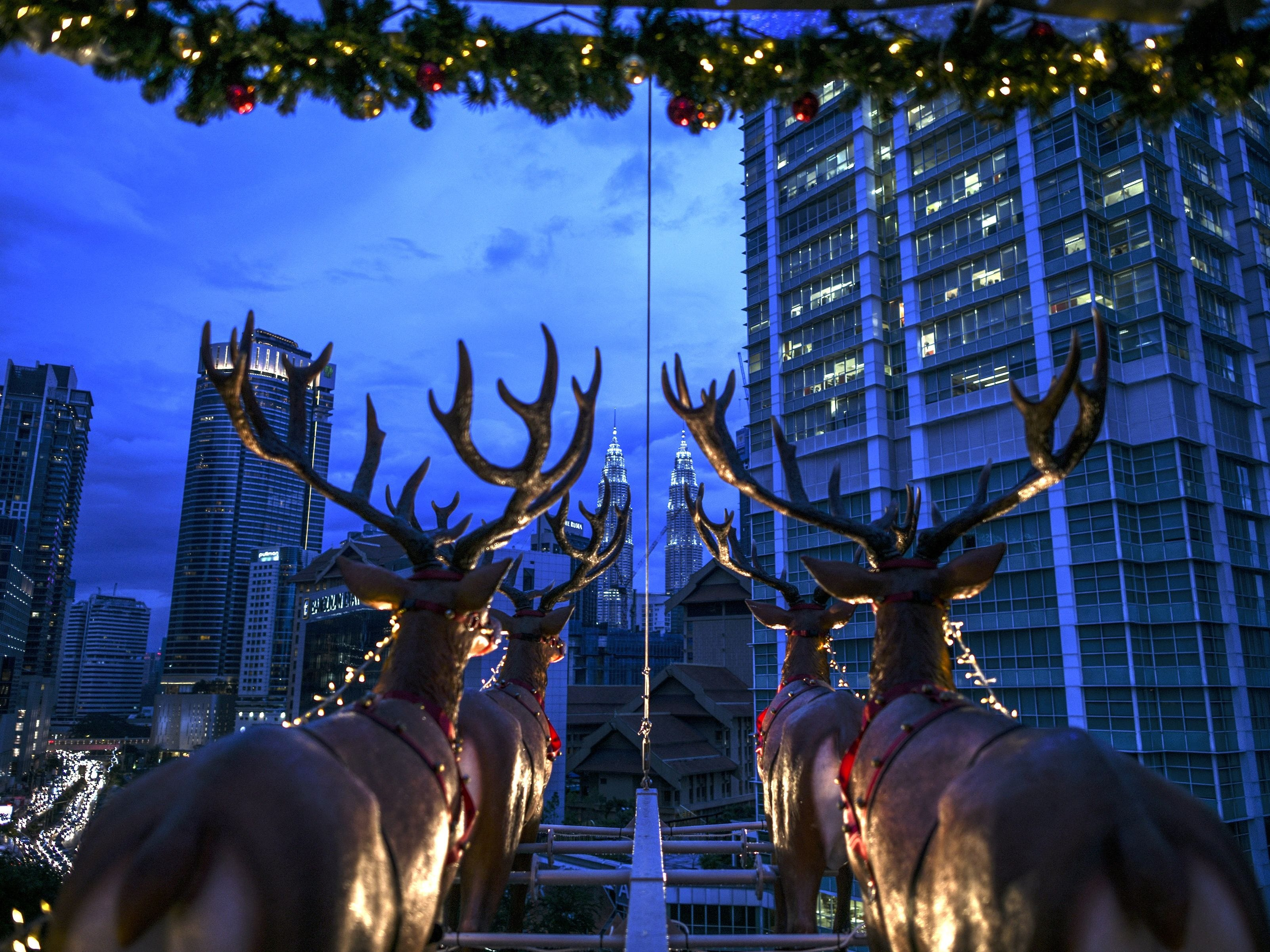 A hanging restaurant is shown on Dec. 5, 2018. It is suspended by a crane overlooking the skyline of Kuala Lumpur, and is inspired by Santa Claus traveling on a sleigh with reindeer for a Christmas season promotion. Strapped into rollercoaster-like seats, the Santa in the Sky patrons dine and drink next to prancing reindeer models and a mannequin of jolly St Nicholas while busy traffic streams nearby below.