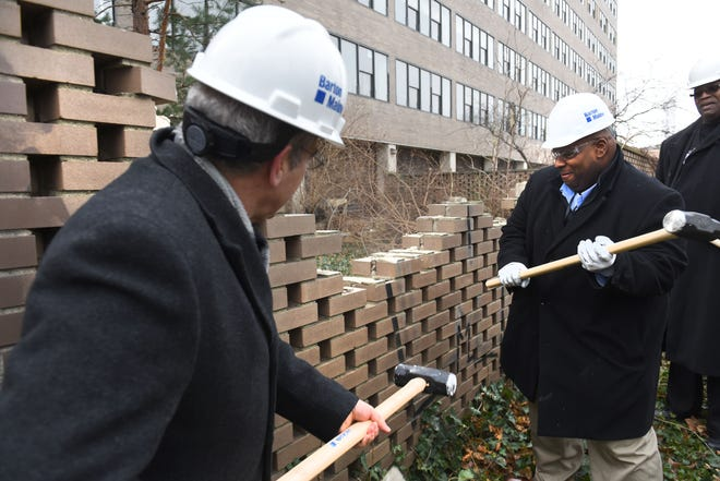Amin Irving, president and CEO ofGinosko Development Co., center, uses a sledgehammer to a wall at the Lafayette West development on Thursday.