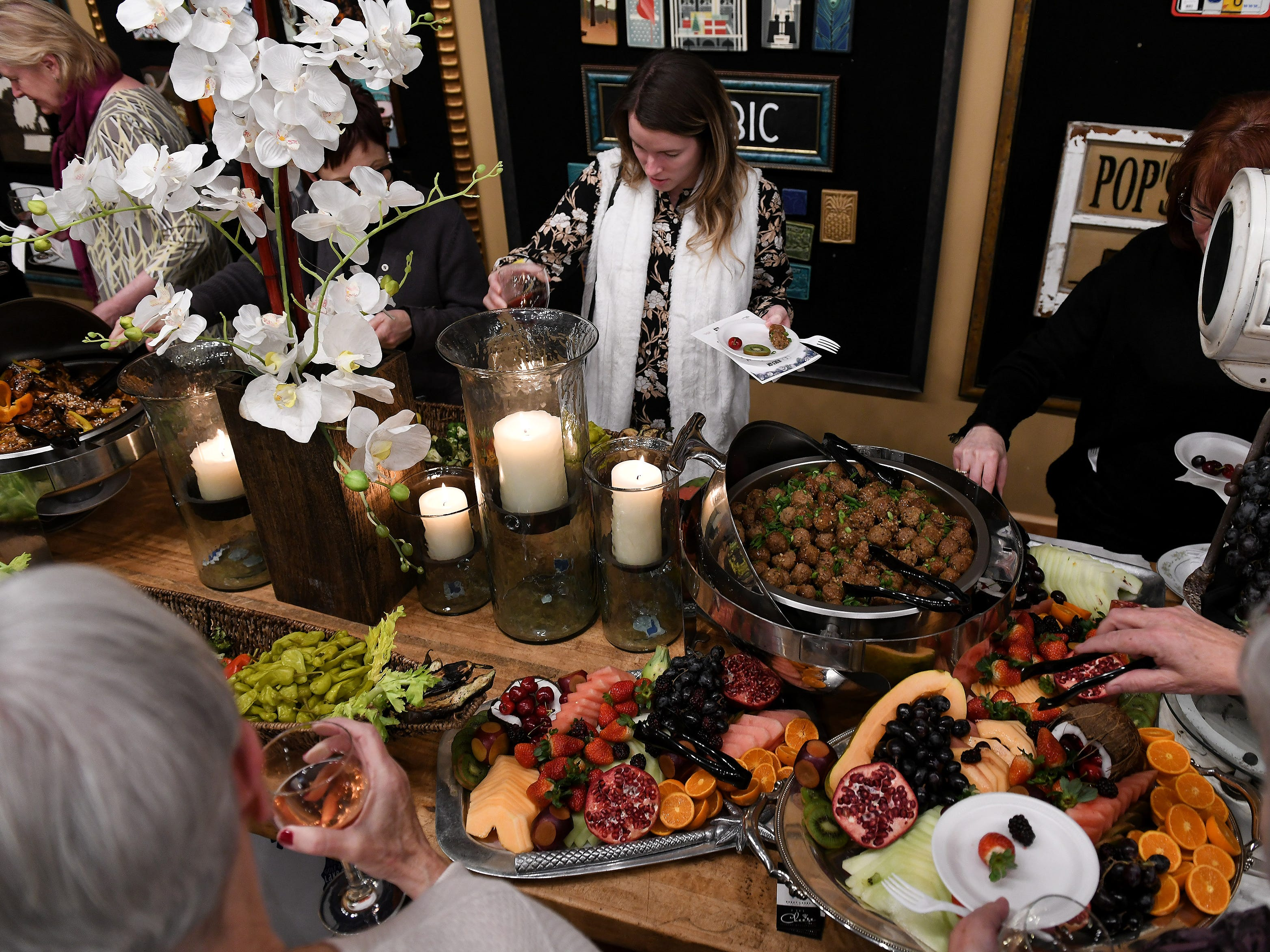 Attendees including Caitlin Bechard of Clarkson, center, partake in the appetizers prepared by Craft Creative Catering.