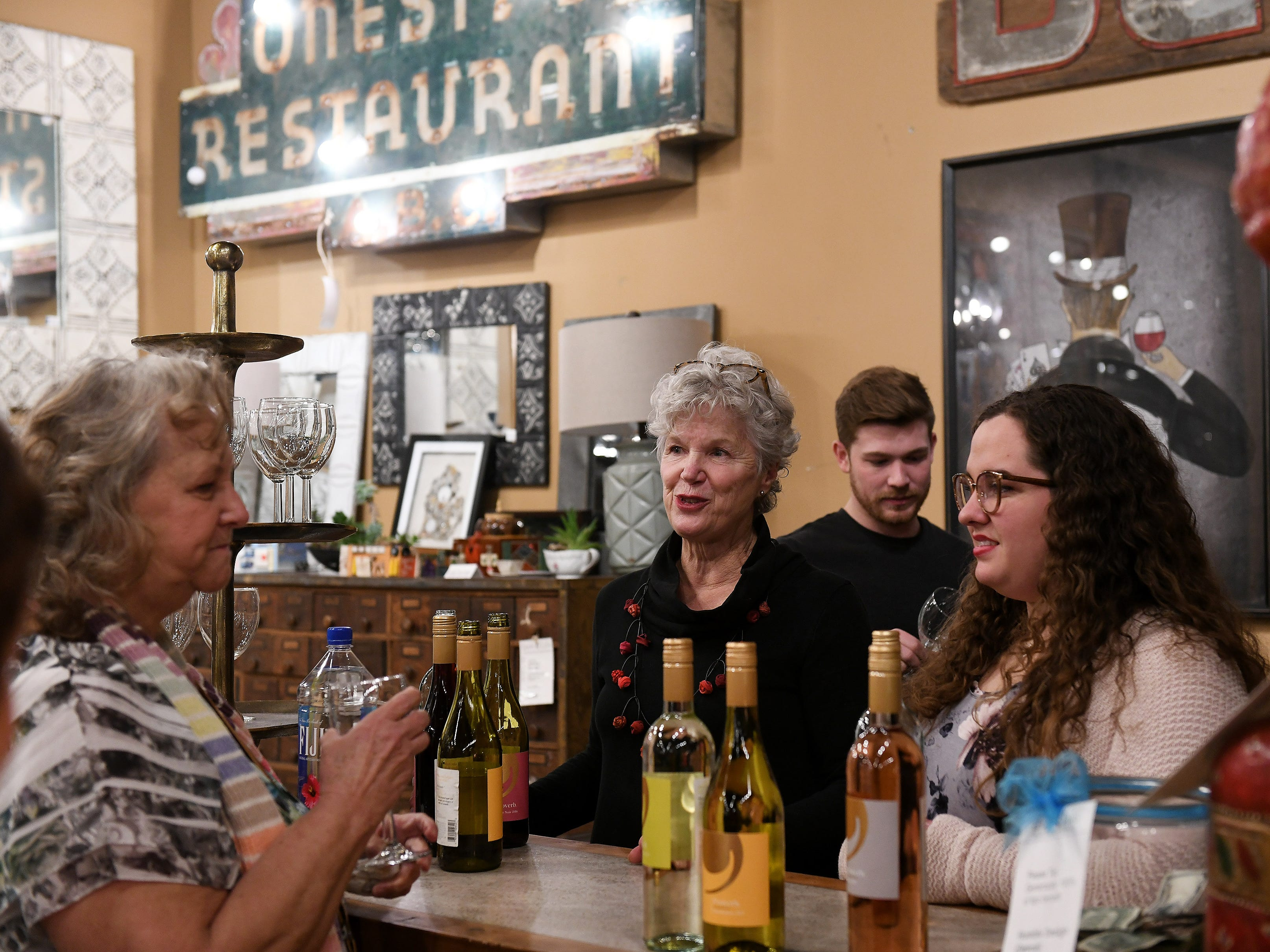 Kate Lawson, former food writer at The Detroit News, center, serves wine.