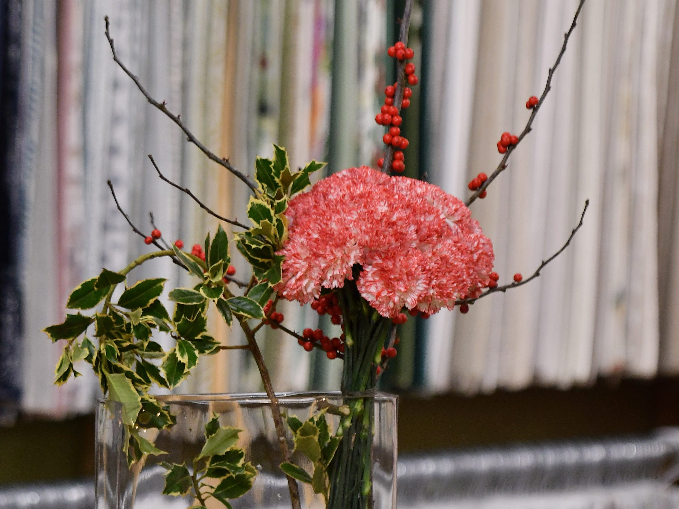 Jeffrey Jucewicz of Jeffrey Floral Architecture shows how simple and elegant a centerpiece can be made, this one with carnations and holly.