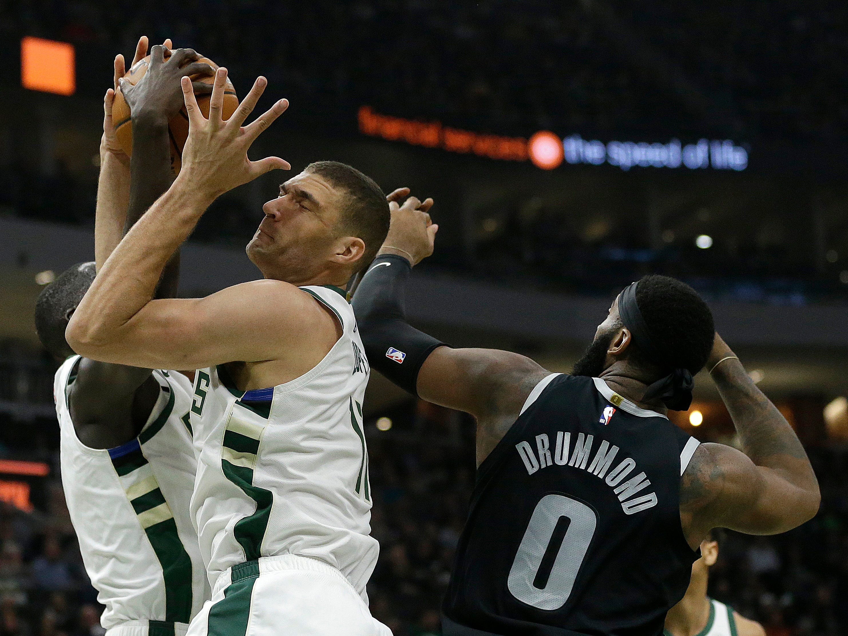 Milwaukee's Brook Lopez, middle, and Thon Maker, left, fight for a rebound with Detroit's Andre Drummond.