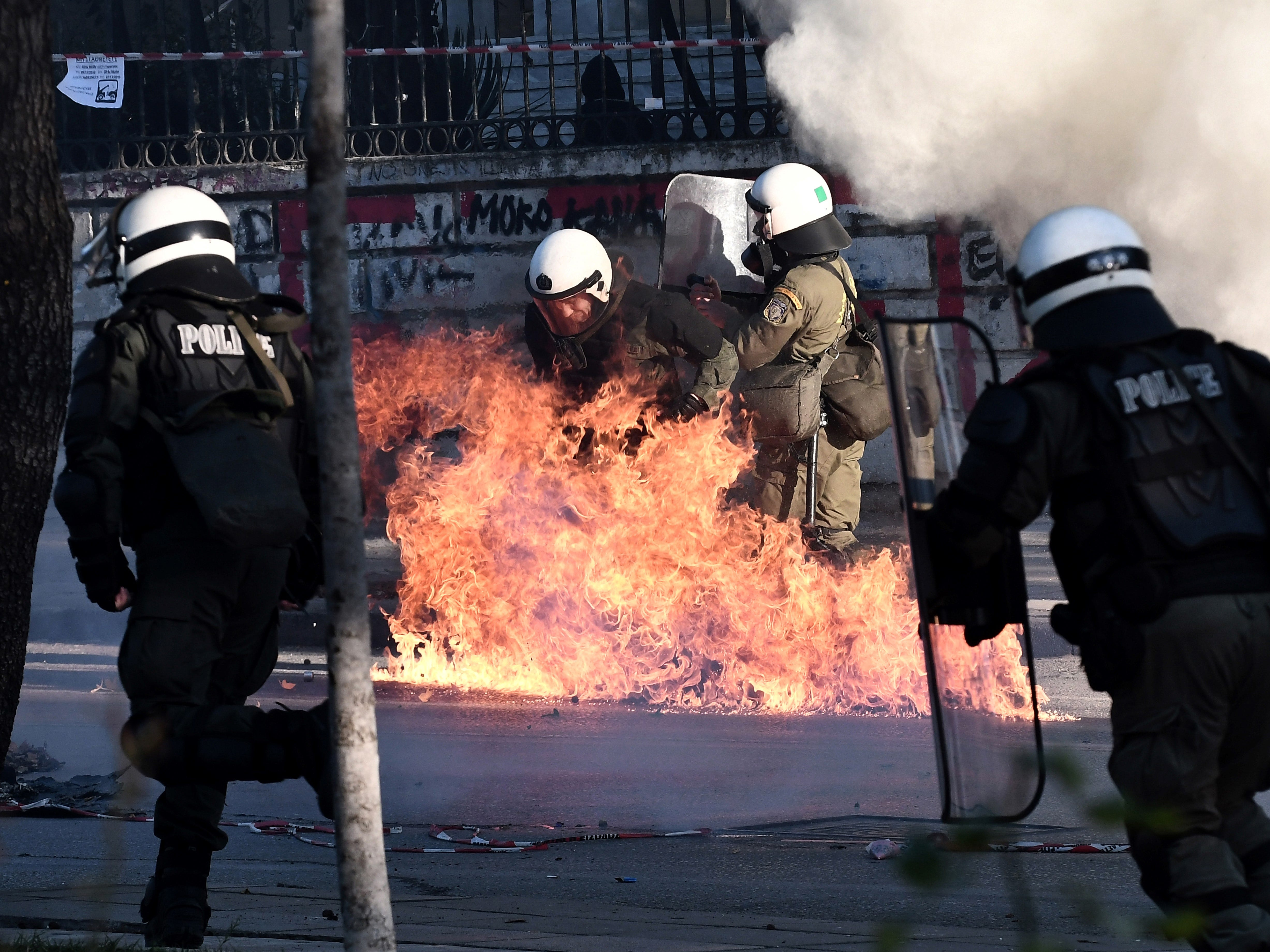 Gasoline bombs explode next to riot police officers during a demonstration in Athens on Dec. 6, 2018 to mark the 10th anniversary of the fatal shooting of a teenager which sparked major riots in Greece in 2008.