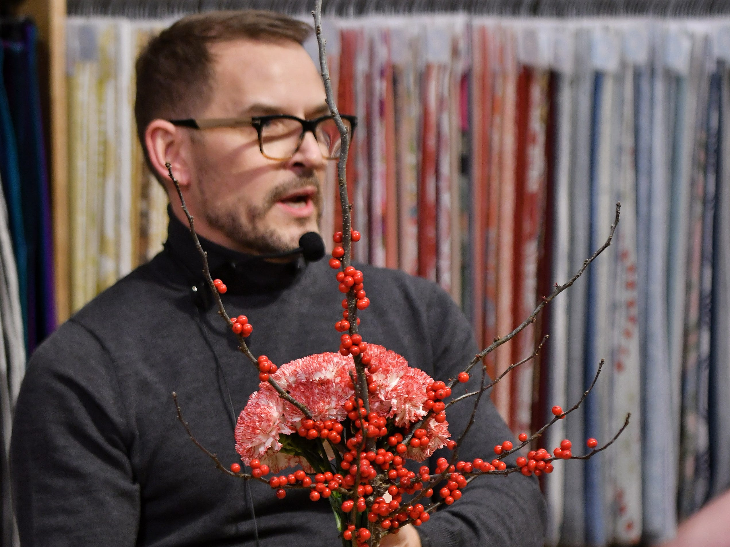 Jeffrey Jucewicz of Jeffrey Floral Architecture shows how simple and elegant a centerpiece can be made, this one with carnations and holly, at the Home for the Holidays installment of the Detroit News Dish & Design event at Leon & Lulu in Clawson, Mich. on Dec. 5, 2018.