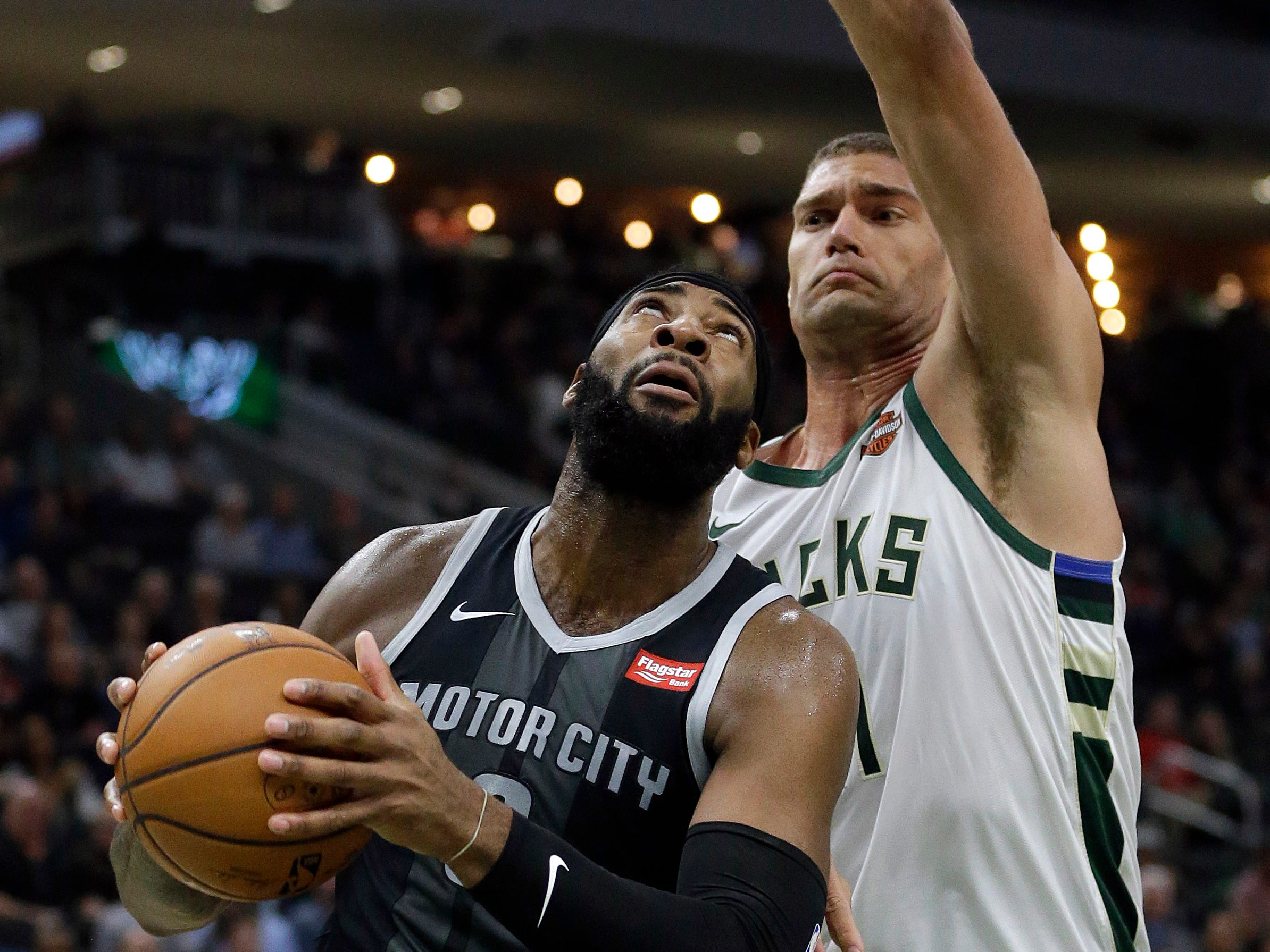 Detroit's Andre Drummond, left, looks to shoot past Milwaukee's Brook Lopez, right, during the first half.