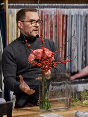 Jeffrey Jucewicz of Jeffrey Floral Architecture shows how simple and elegant a centerpiece can be made, this one with carnations and holly, at the holiday installment of the Detroit News Dish & Design event at Leon & Lulu in Clawson, Mich. on Dec. 5, 2018.